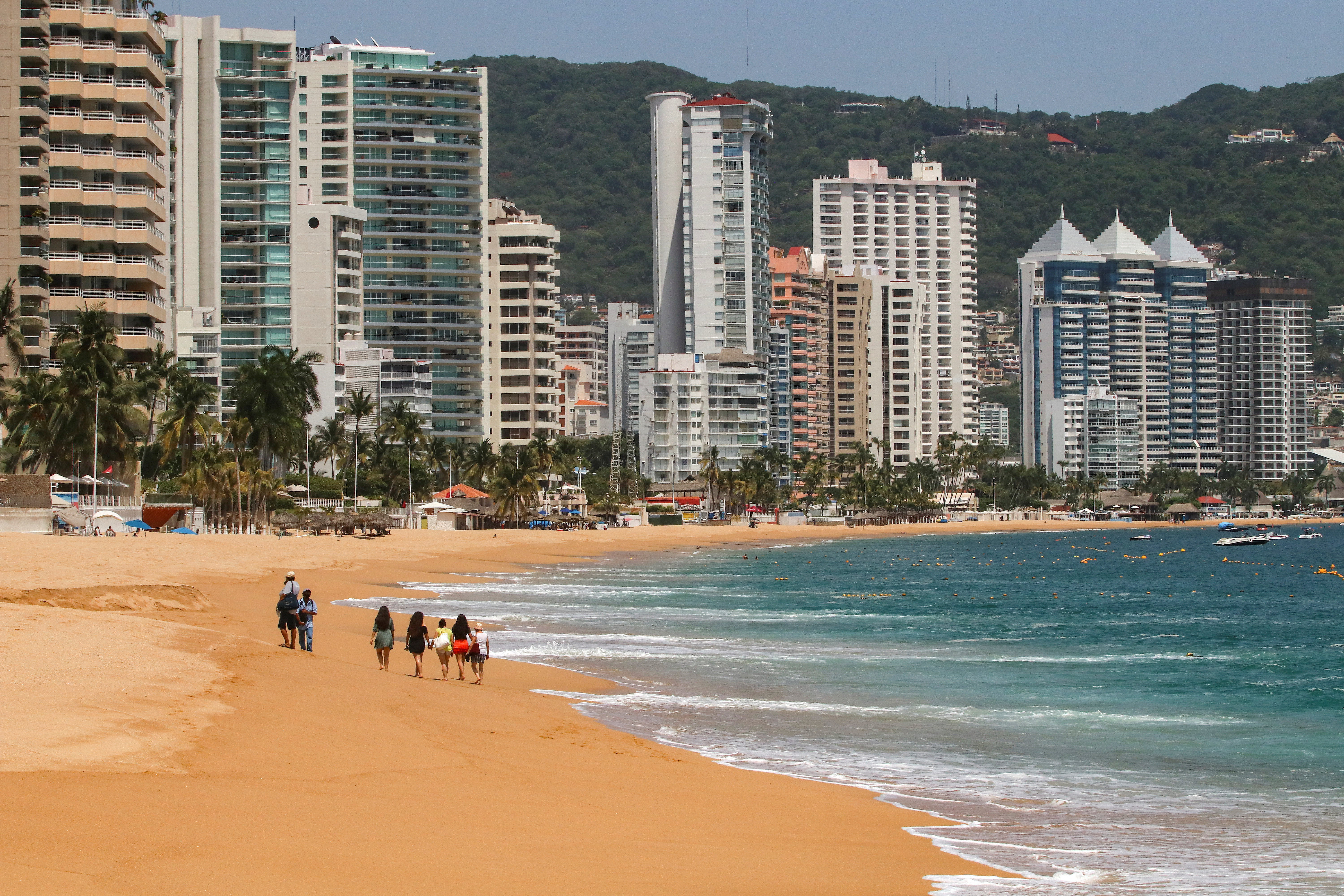 Tourists walk along a beach during the reopening of the beaches and hotels after confinement measures were eased this week, as the coronavirus disease (COVID-19) outbreak continues in Acapulco, Mexico July 2, 2020.