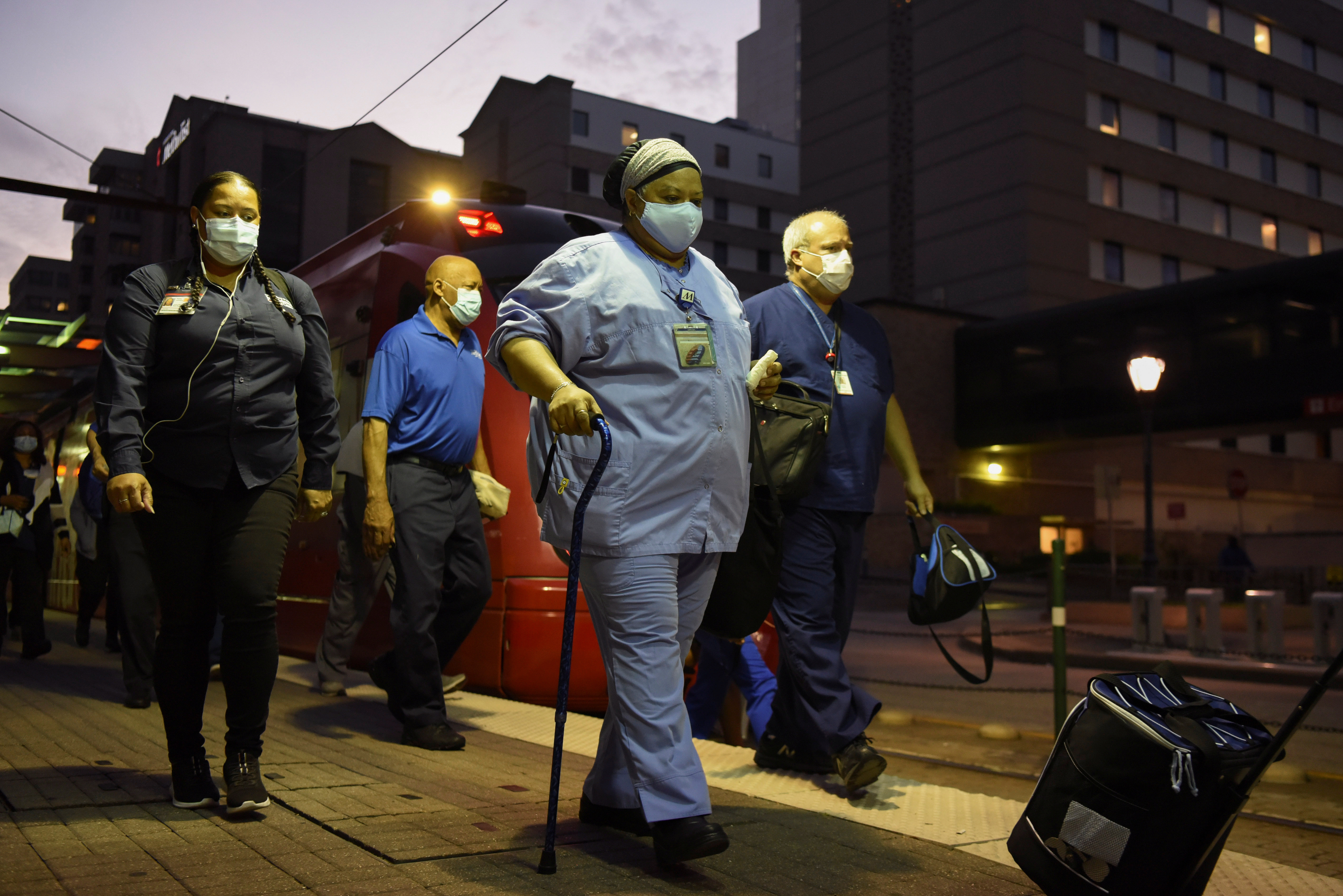 Healthcare workers walk through the Texas Medical Center during a shift change as cases of the coronavirus disease (COVID-19) spike in Houston, Texas, U.S., July 8, 2020.  REUTERS/Callaghan O'Hare - RC25PH93WYMO