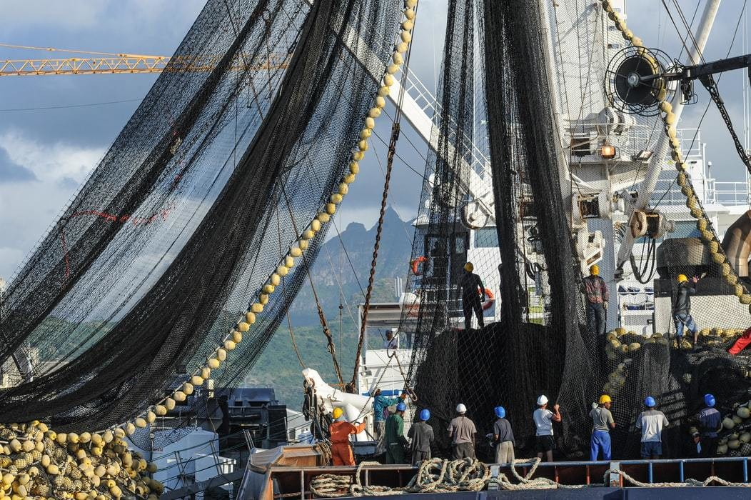 A large fishing ship is seen preparing its fishing nets before going out to sea.