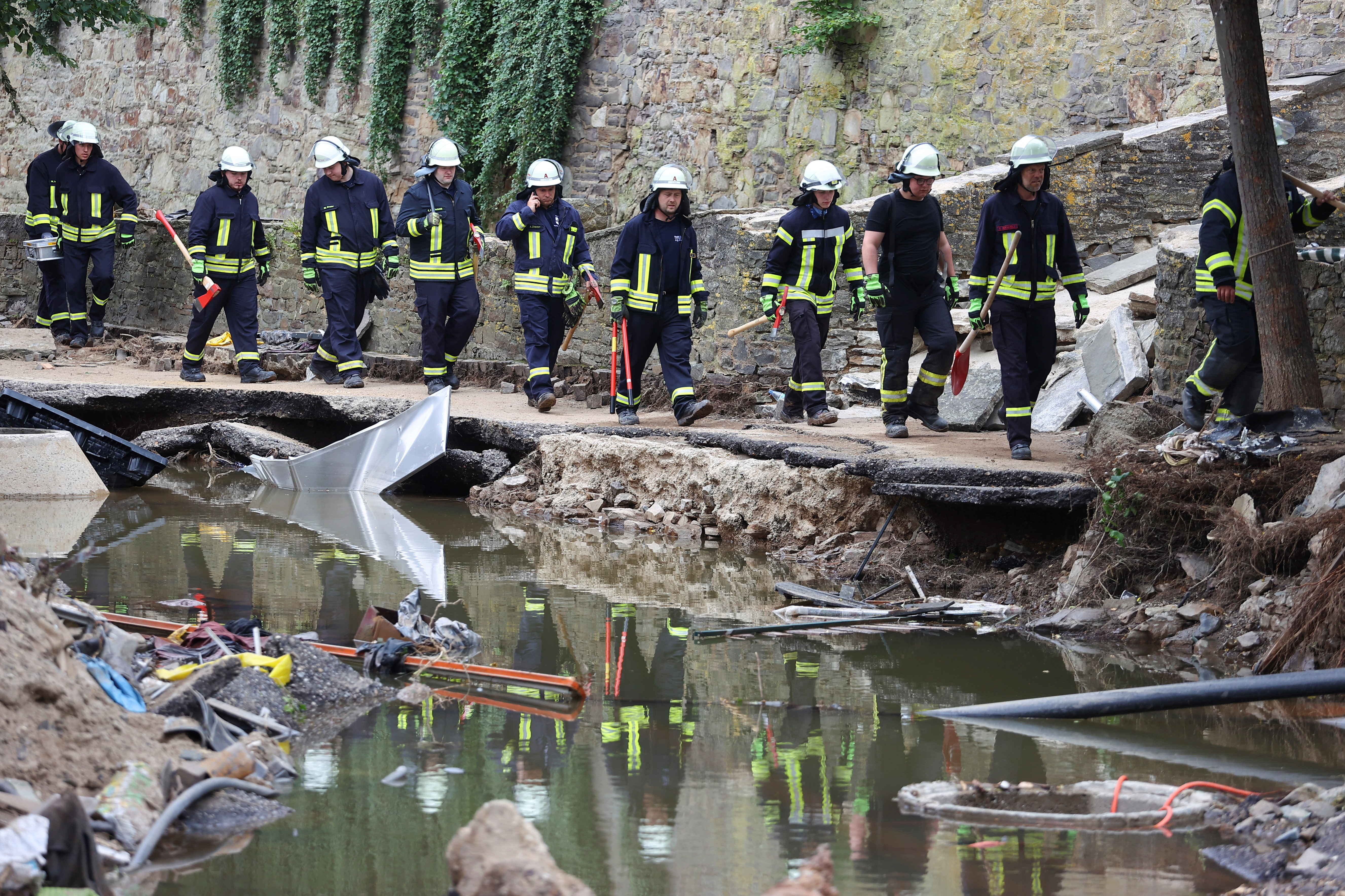 firefighters walk in an area affected by floods caused by heavy rainfalls in Bad Muenstereifel, Germany.
