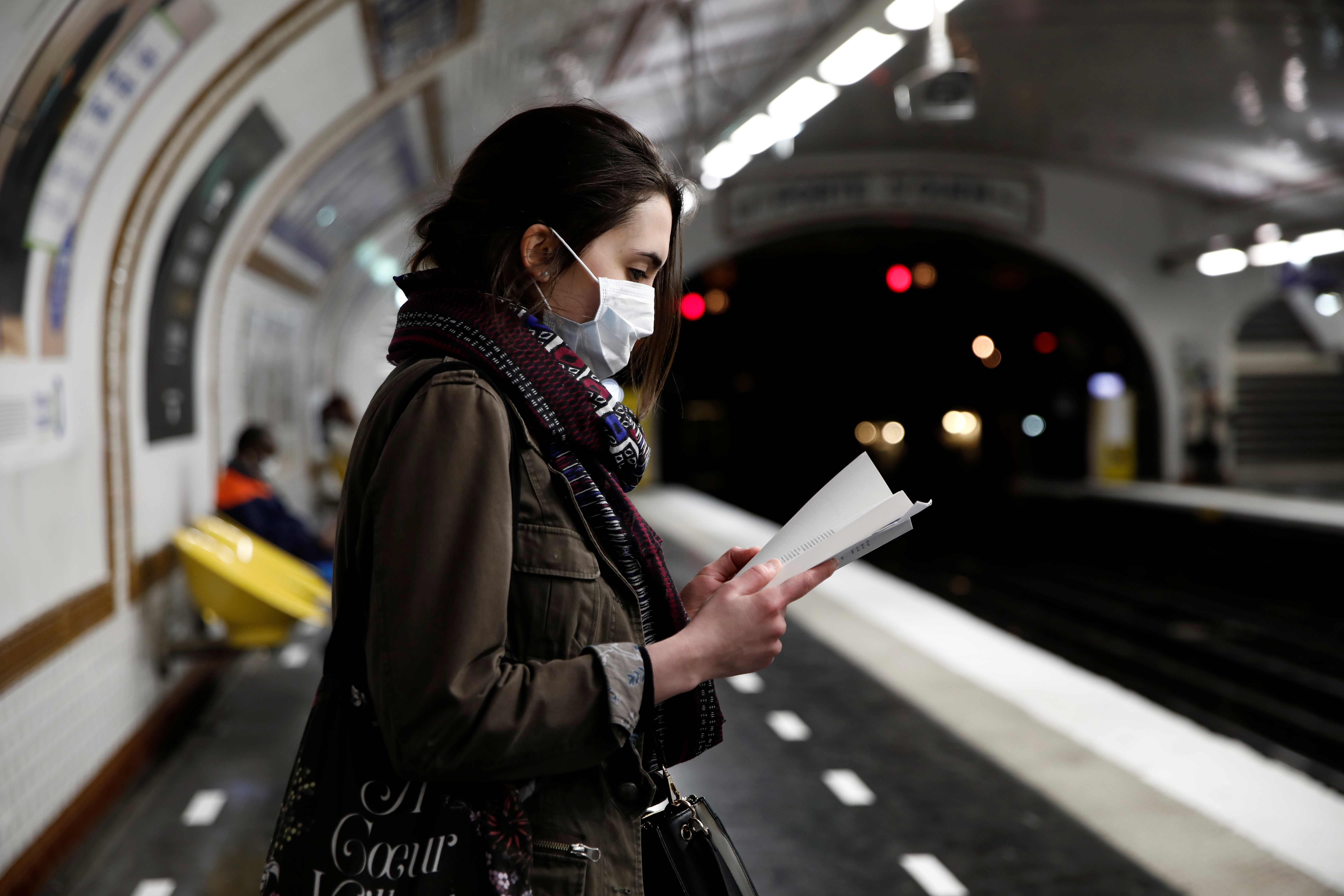 A woman wearing a protective face mask reads a book on a platform at a metro station of Paris transport network (RATP) during the outbreak of the coronavirus disease (COVID-19) in Paris, France, May 5, 2020. REUTERS/Benoit Tessier - RC2EIG9NNACY