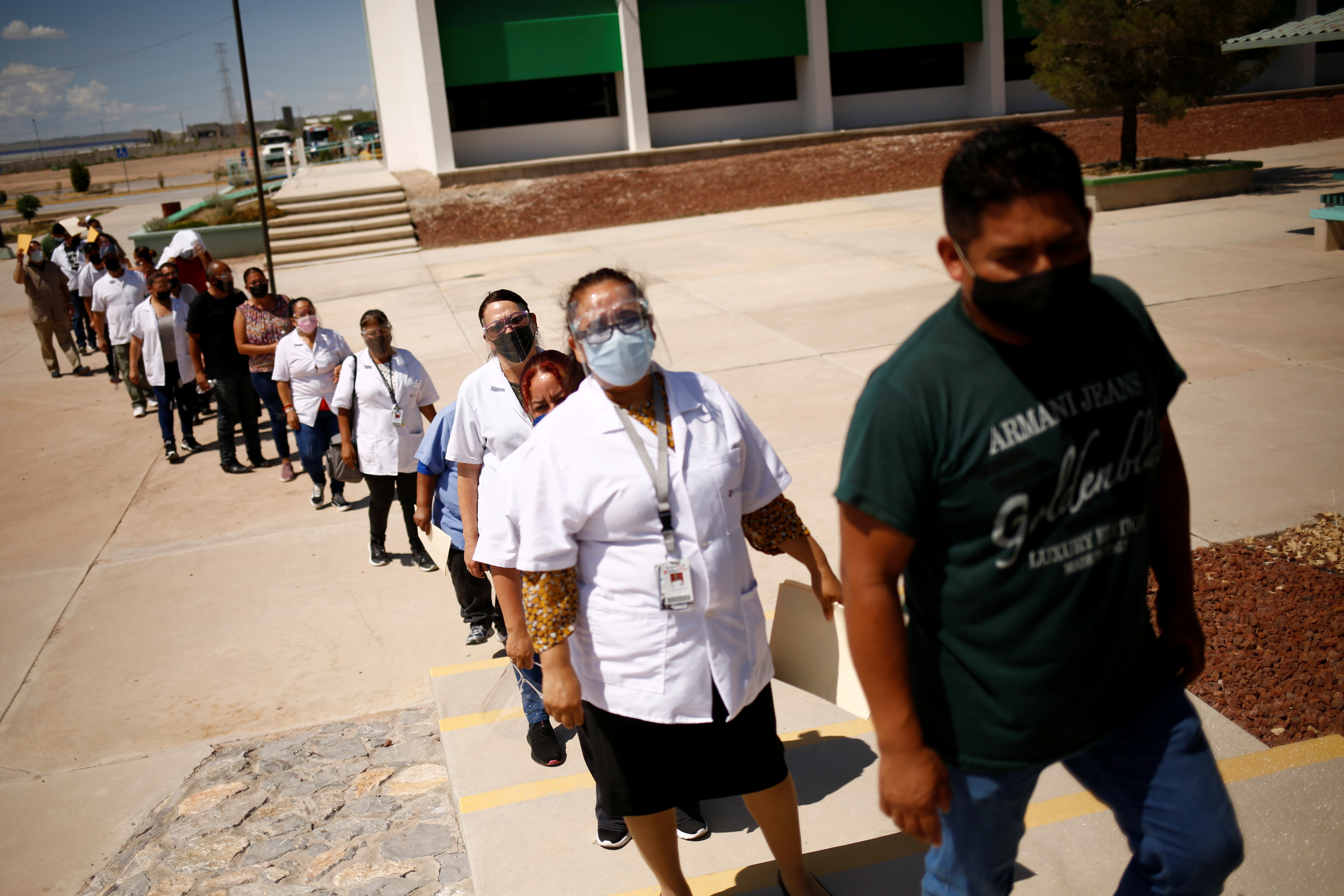 Employees of an assembly factory queue to receive a dose of the Pfizer-BioNTech coronavirus disease (COVID-19) vaccine during a mass vaccination program for people over 40 years of age at a university in Ciudad Juarez, Mexico July 5, 2021. REUTERS/Jose Luis Gonzalez - RC2FEO9TUDY4