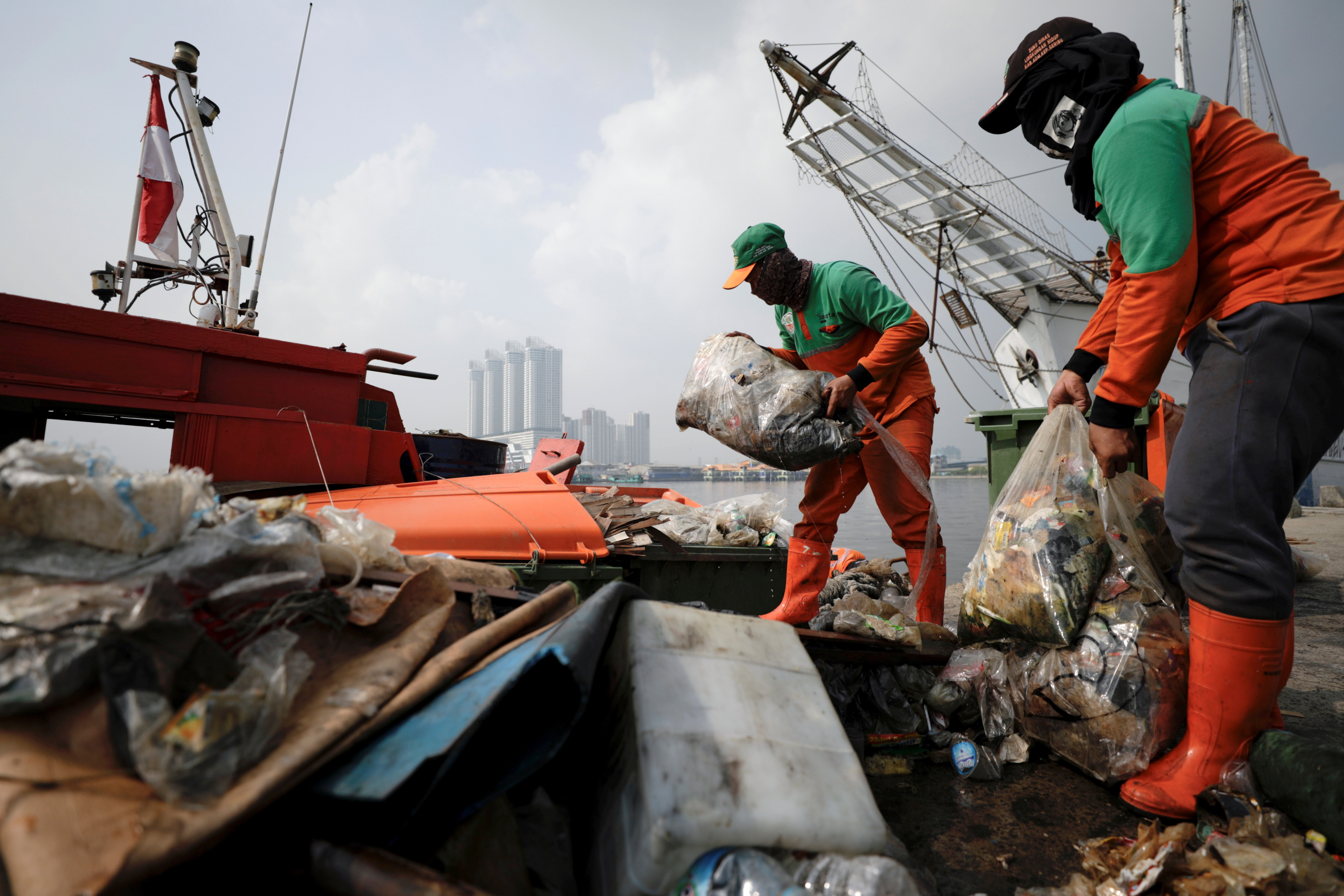 Municipality workers unload bags of garbage collected from the shore, most of it plastics and domestic waste, during World Oceans Day, at Kali Adem Port in Jakarta, Indonesia, June 8, 2021.