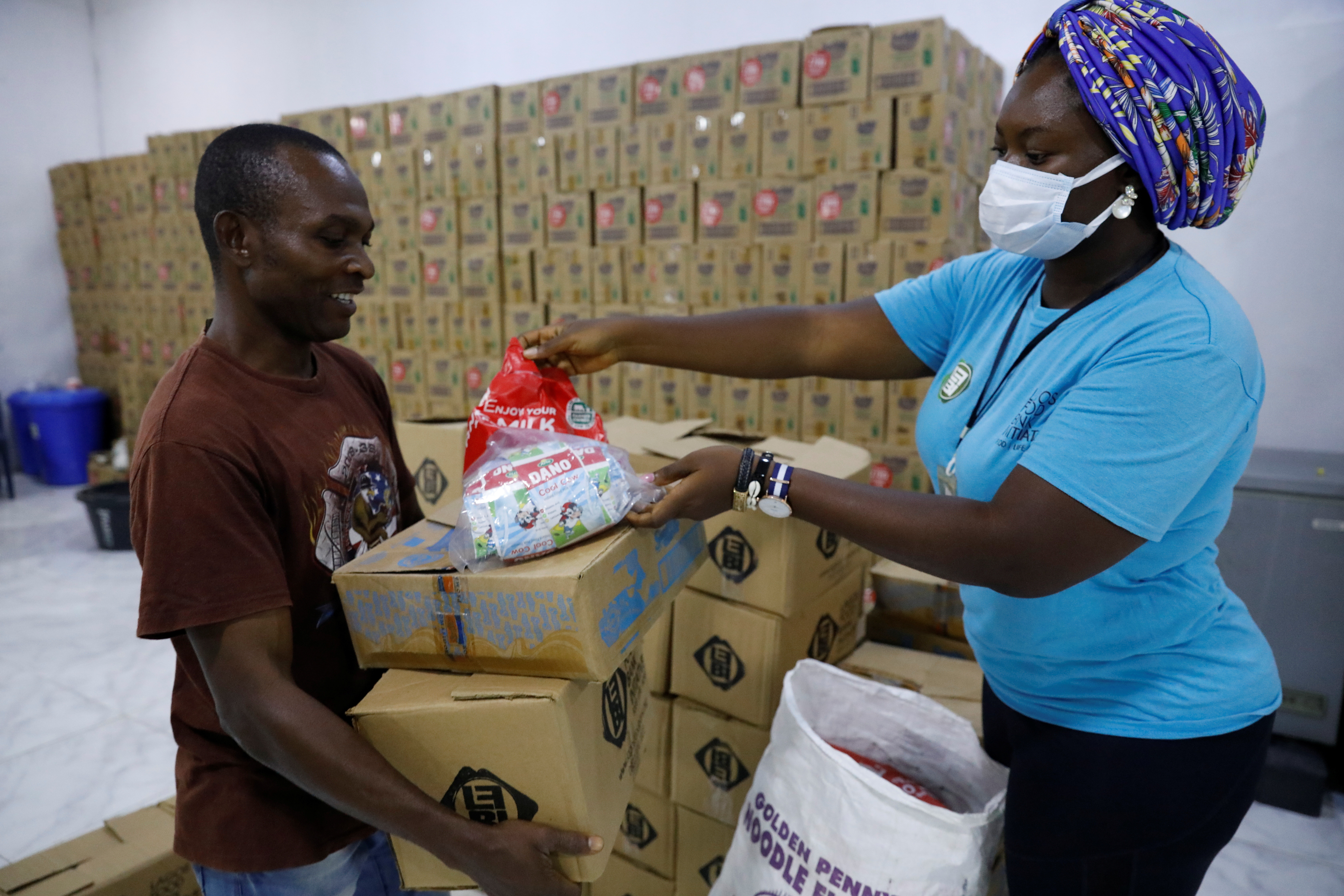 Desmond Okorie, a beneficiary of the food aid distribution by the Lagos food bank inititative, receives food supplies at the food bank warehouse in Lagos, Nigeria July 10, 2021