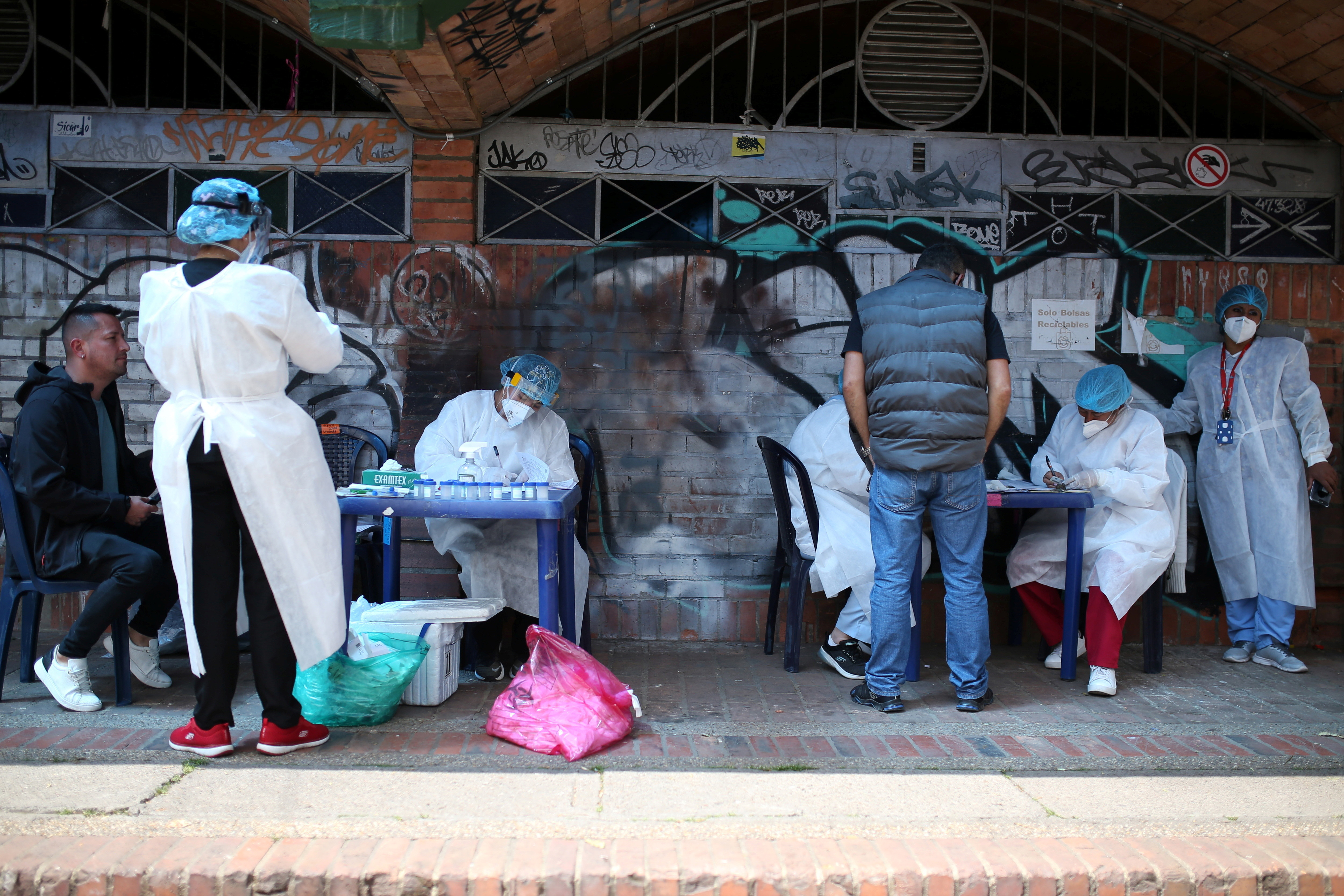 Members of a medical team dressed in personal protective equipment test people for the coronavirus disease in Bogota, Colombia.