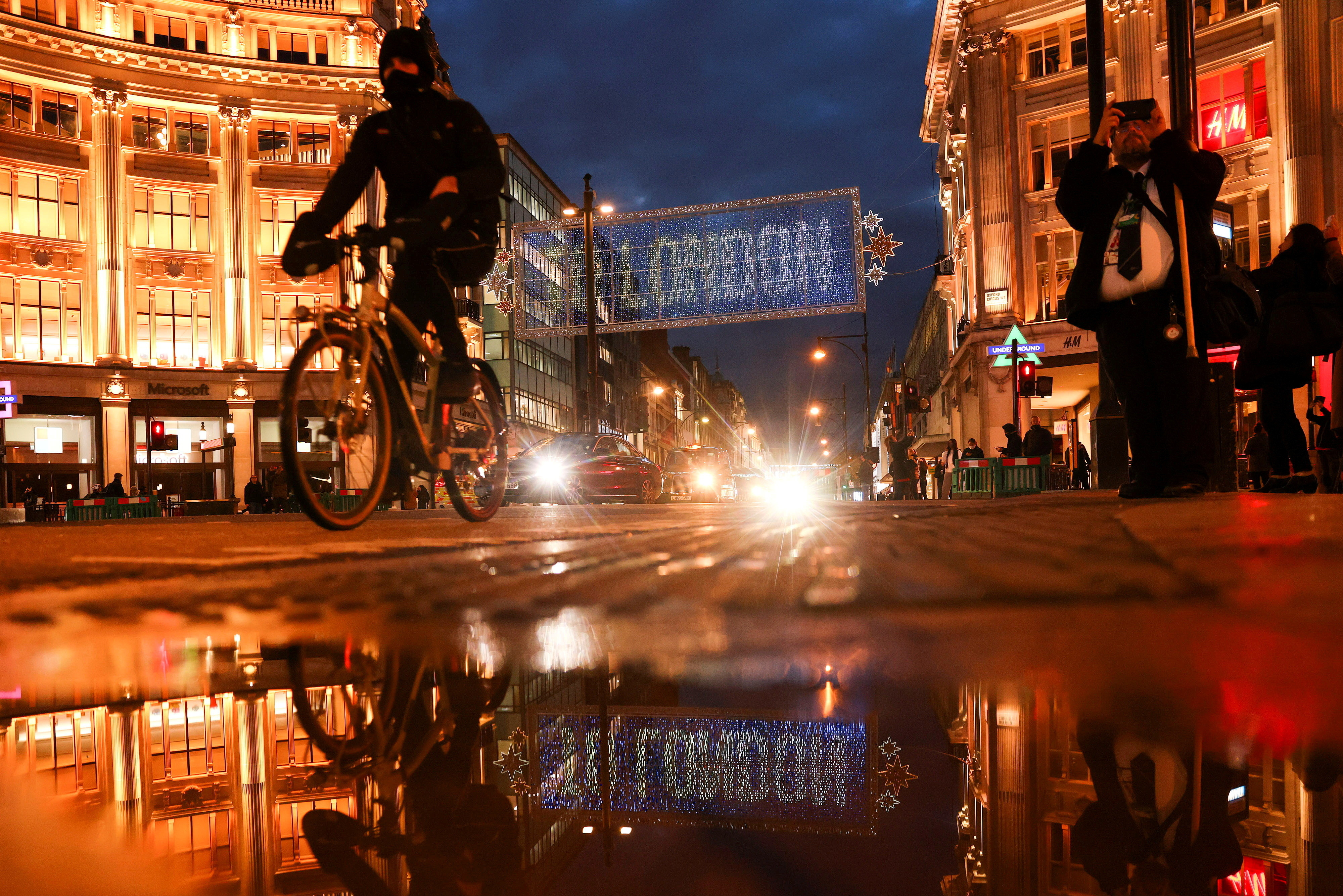 A cyclist moves cycles past the Christmas lights on Oxford Street amid the coronavirus disease (COVID-19) outbreak in London, Britain, November 19, 2020. REUTERS/Simon Dawson     TPX IMAGES OF THE DAY - RC2H6K9IRZS7
