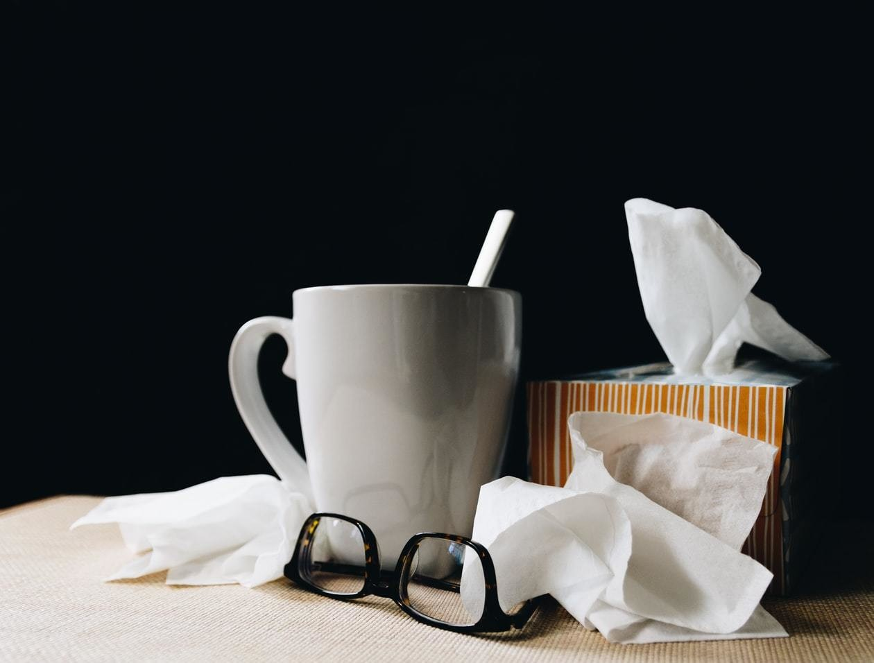 Tissues, glasses and a coffee cup are seen on a table.