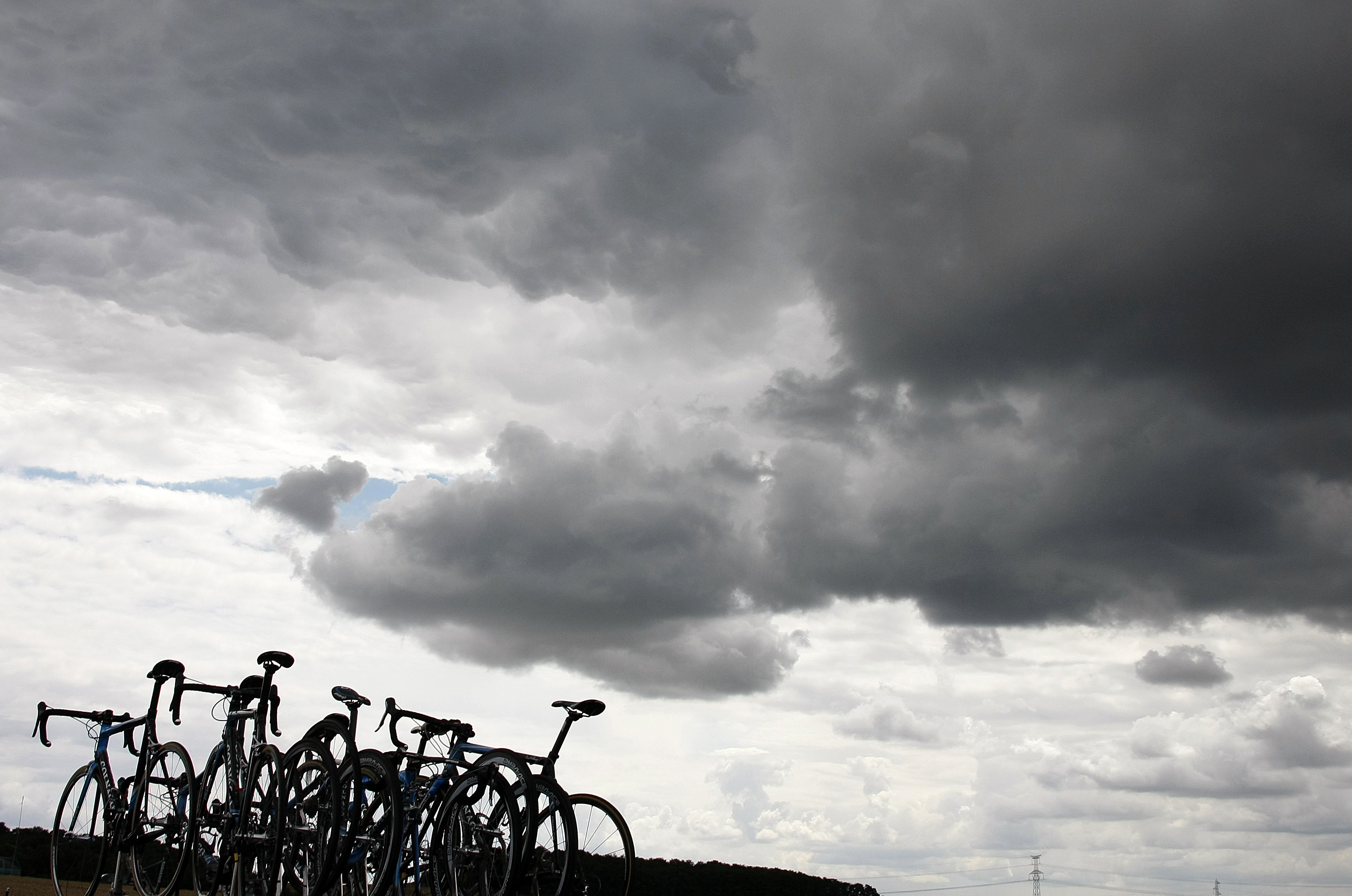Bicycles are seen under storm clouds