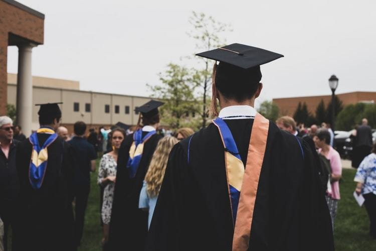 image of people in their caps and gowns attending a college graduation ceremony
