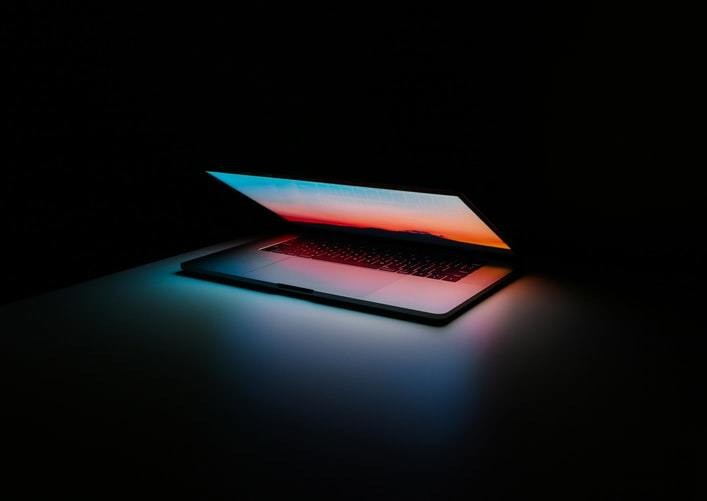 Light coming from an open lap top in a dark room