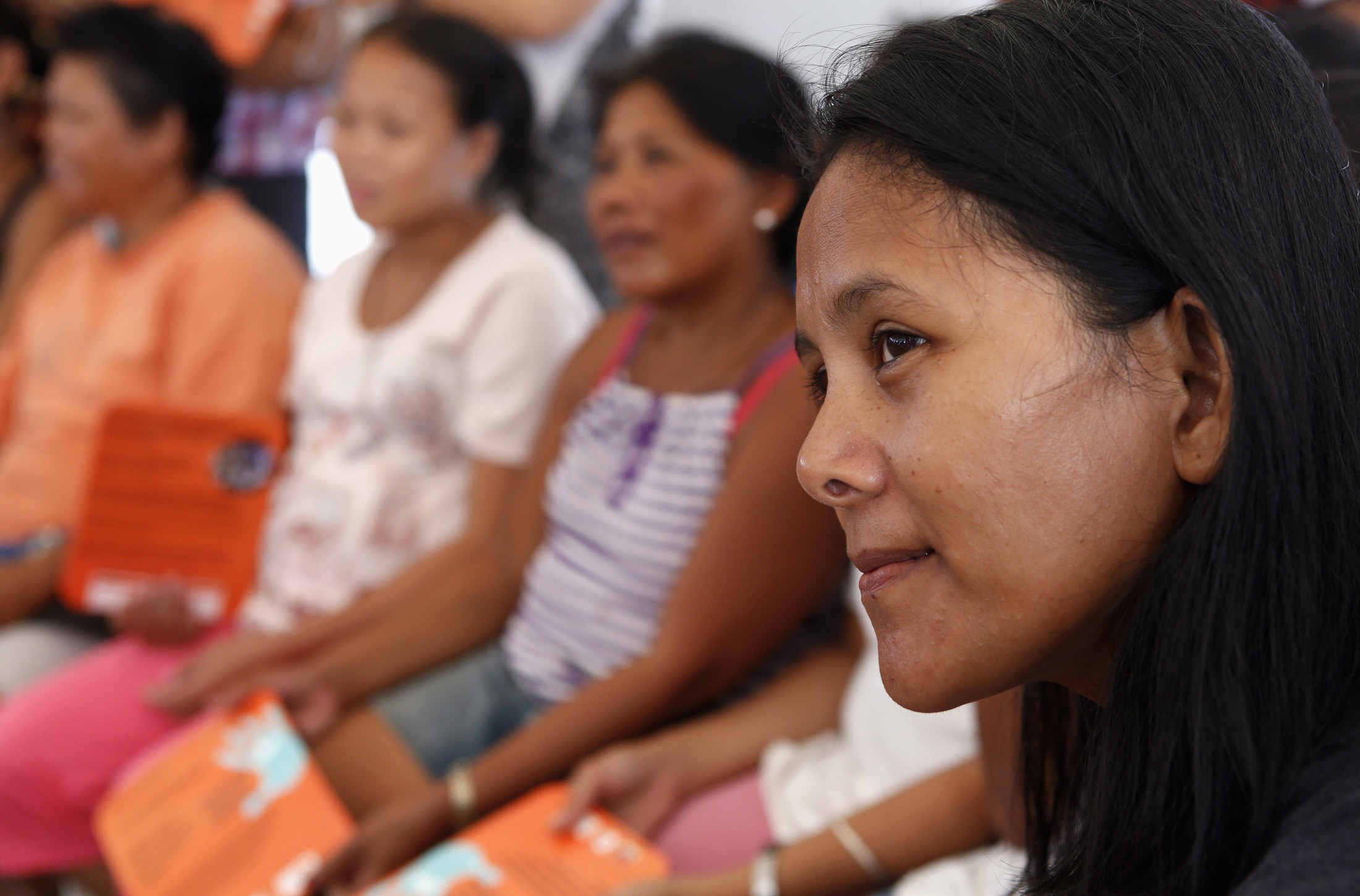 Women survivors of super typhoon Haiyan listen during a lecture on the prevention of gender-based violence by United Nations Population Fund (UNFPA) volunteer in Tacloban city in central Philippines December 14, 2013. Based on national data in the eight affected provinces prior to the disaster, an estimated 375,000 women and girls aged 15-49 would have experienced sexual violence in their lifetime. This number could increase by 75,000 without adequate protection measures, UNFPA said in a statement.   REUTERS/Erik De Castro (PHILIPPINES - Tags: DISASTER HEALTH) - GM1E9CE1FG601
