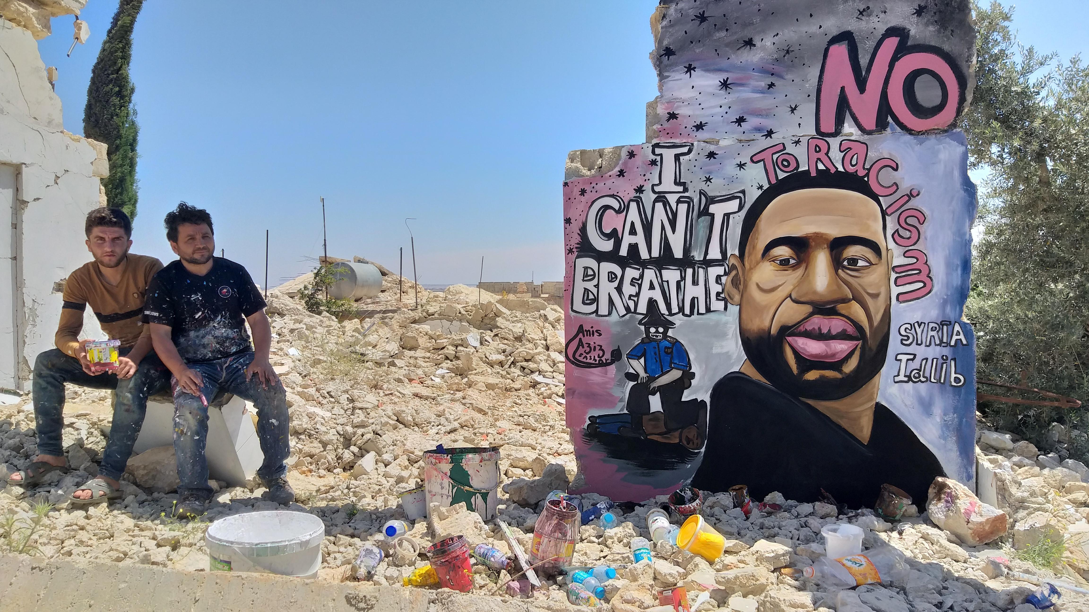 Artists Aziz Asmr and Anis Hamdoun pose next to a graffiti of George Floyd in Idlib, Syria June 1, 2020.