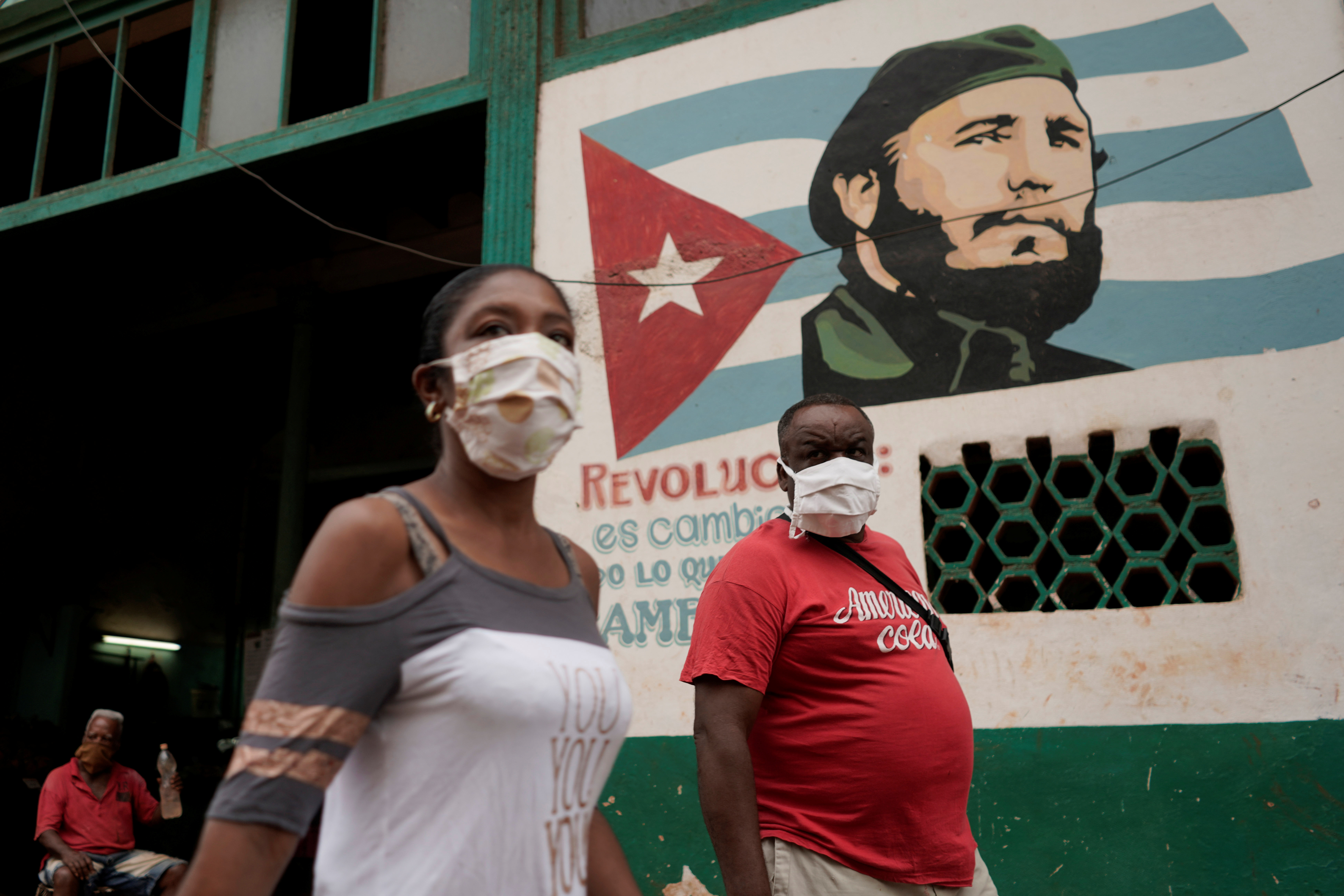 People pass by an image of late Cuban President Fidel Castro amid concerns about the spread of the coronavirus disease (COVID-19), in Havana, Cuba, July 19, 2020. REUTERS/Alexandre Meneghini - RC2HWH9FDQ70