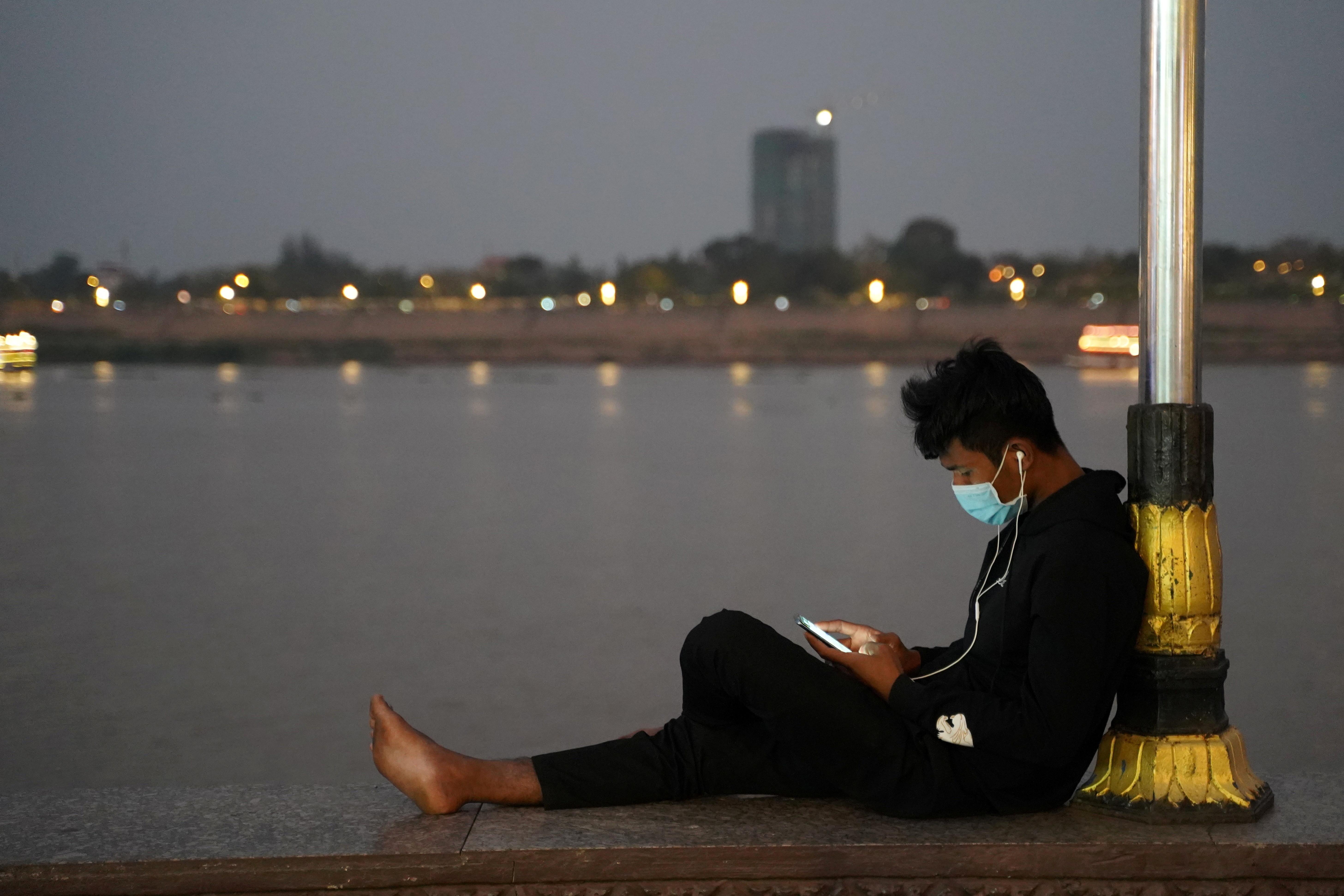 A man uses his mobile phone on the Tonle Sap riverside amid the coronavirus pandemic in Phnom Penh, Cambodia, February 18, 2021. REUTERS/Cindy Liu - RC23VL96NFB3