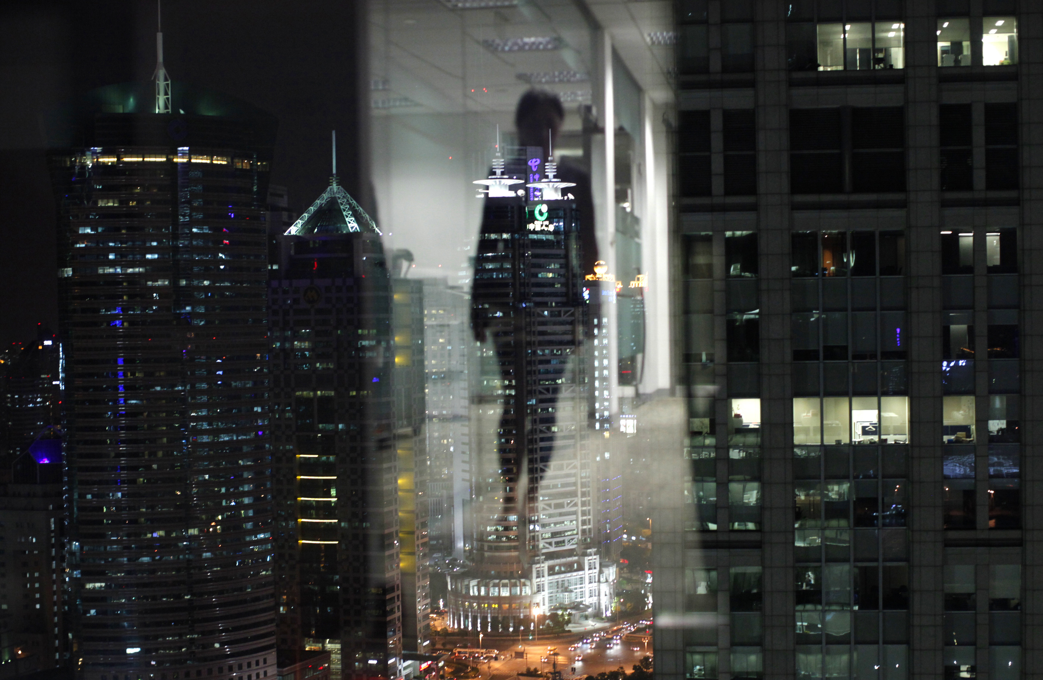A woman is reflected in a window of an office in the financial district of Pudong in Shanghai September 22, 2011. REUTERS/Carlos Barria (CHINA - Tags: CITYSPACE SOCIETY) - RTR2RVTO