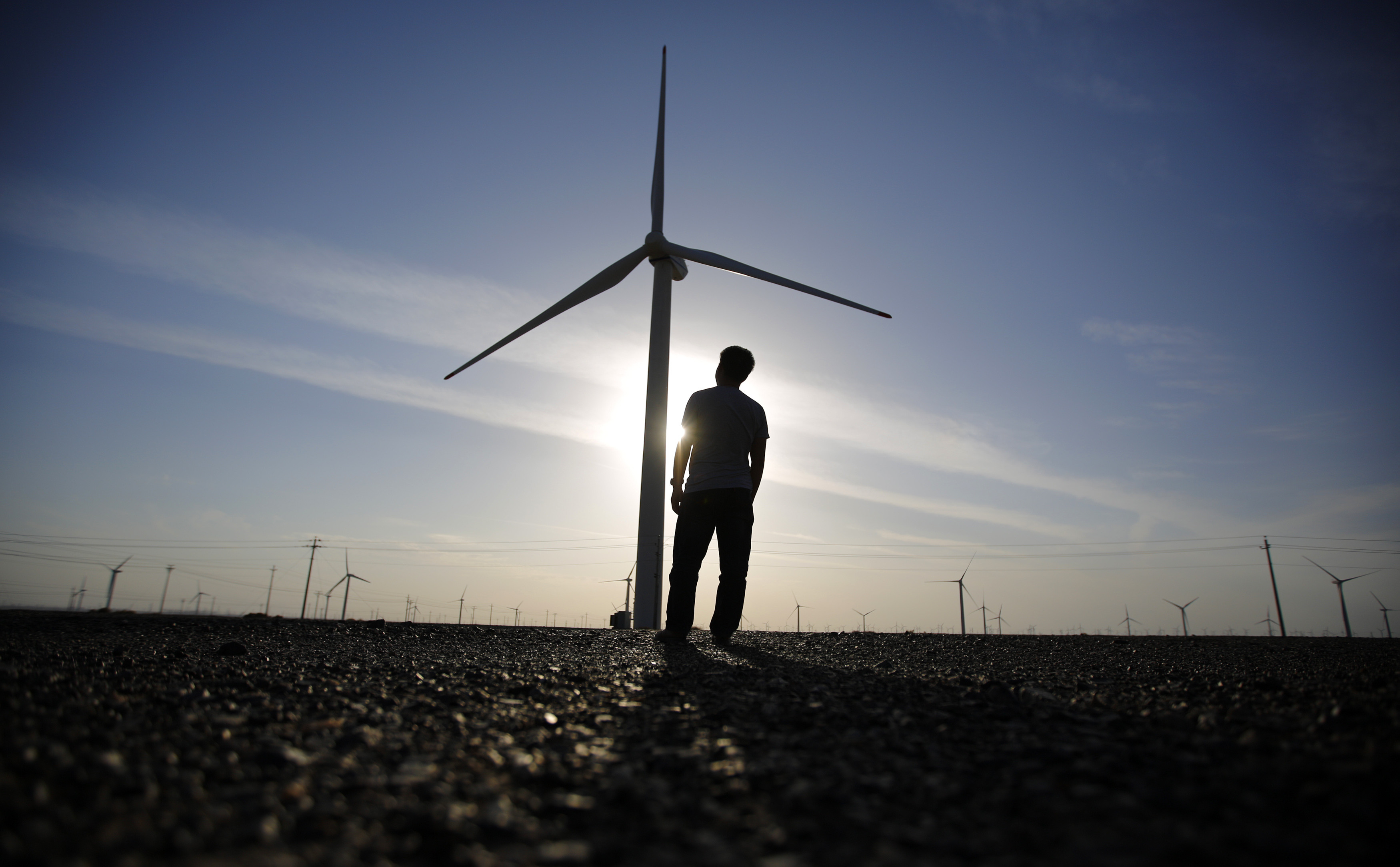 A worker stands as he looks at a wind turbine used to generate electricity, at a wind farm in Guazhou, 950km (590 miles) northwest of Lanzhou, Gansu Province September 15, 2013. China is pumping investment into wind power, which is more cost-competitive than solar energy and partly able to compete with coal and gas. China is the world's biggest producer of CO2 emissions, but is also the world's leading generator of renewable electricity. Environmental issues will be under the spotlight during a working group of the Intergovernmental Panel on Climate Change, which will meet in Stockholm from September 23-26. Picture taken September 15, 2013. REUTERS/Carlos Barria  (CHINA - Tags: ENERGY BUSINESS ENVIRONMENT) - GM1E99M14RE01