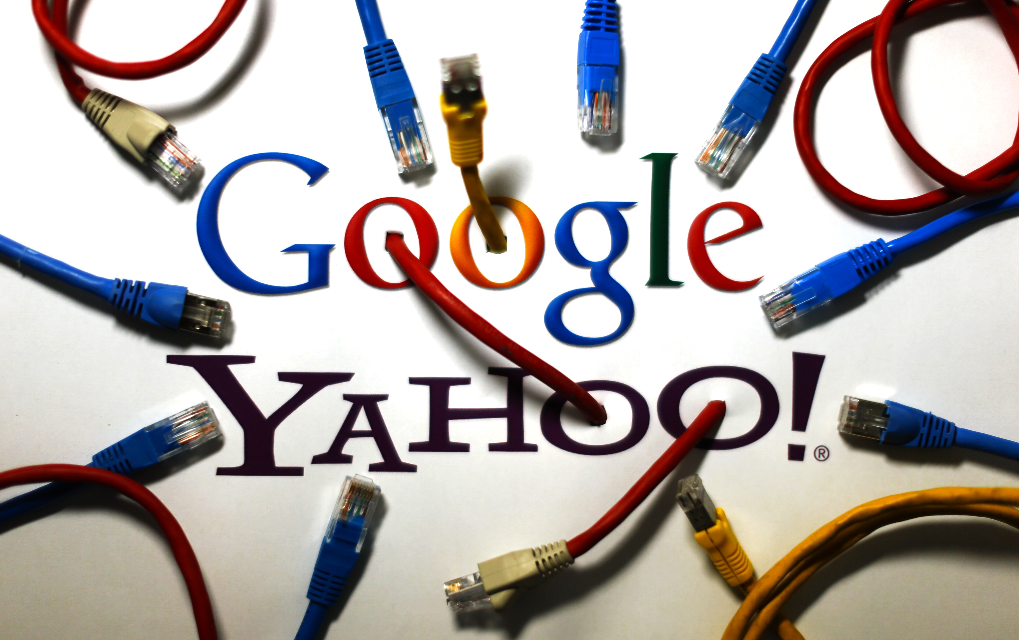 An illustration picture shows the logos of Google and Yahoo connected with LAN cables in a Berlin office October 31, 2013. The National Security Agency has tapped directly into communications links used by Google and Yahoo to move huge amounts of email and other user information among overseas data centers, the Washington Post reported on Wednesday. The report, based on secret NSA documents leaked by former contractor Edward Snowden, appears to show the agency has used weak restrictions on its overseas activities to exploit major U.S. companies' data to a far greater extent than realized.  This logo has been updated and is no longer in use.This logo has been updated and is no longer in use.  REUTERS/Pawel Kopczynski (GERMANY - Tags: POLITICS BUSINESS TELECOMS) - BM2E9AV0WDJ01