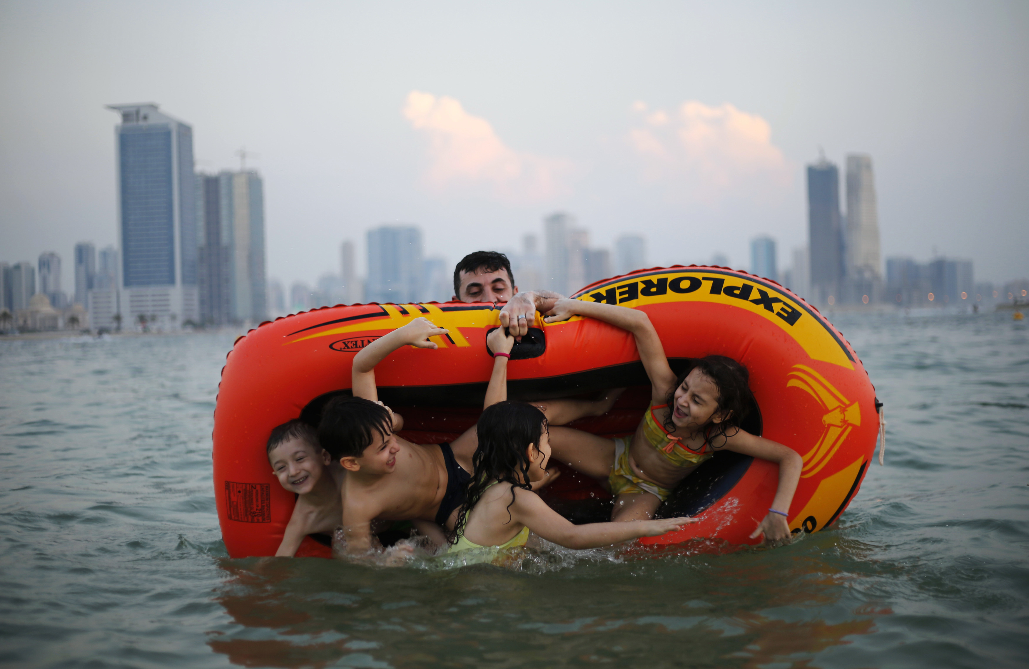 A man plays with his family at Mamzar beach in Dubai October 25, 2013.