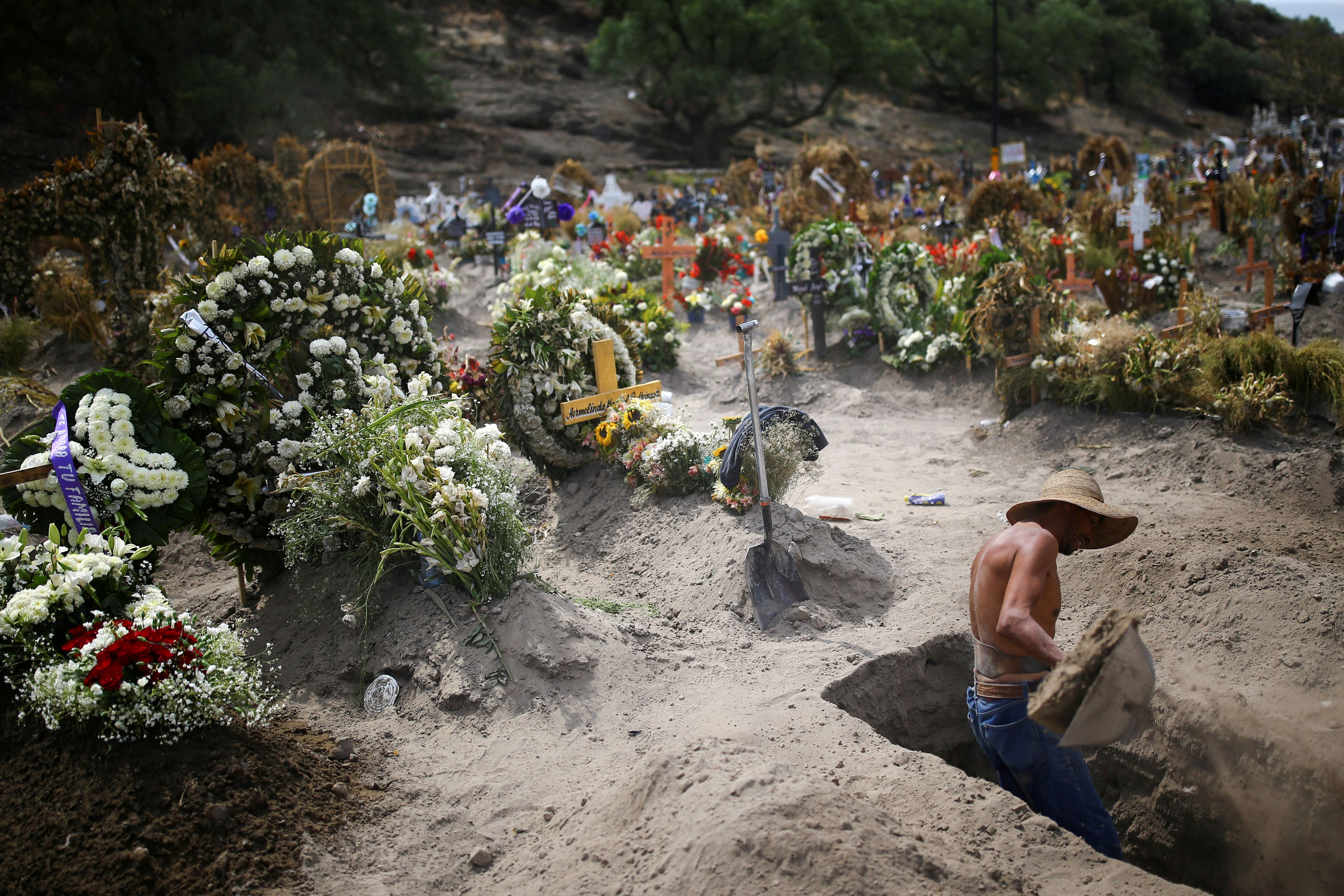 A cemetery worker digs new graves at the Xico cemetery on the outskirts of Mexico City, as the coronavirus disease (COVID-19) outbreak continues in Mexico, June 10, 2020. REUTERS/Edgard Garrido     TPX IMAGES OF THE DAY - RC2O6H9O5G20