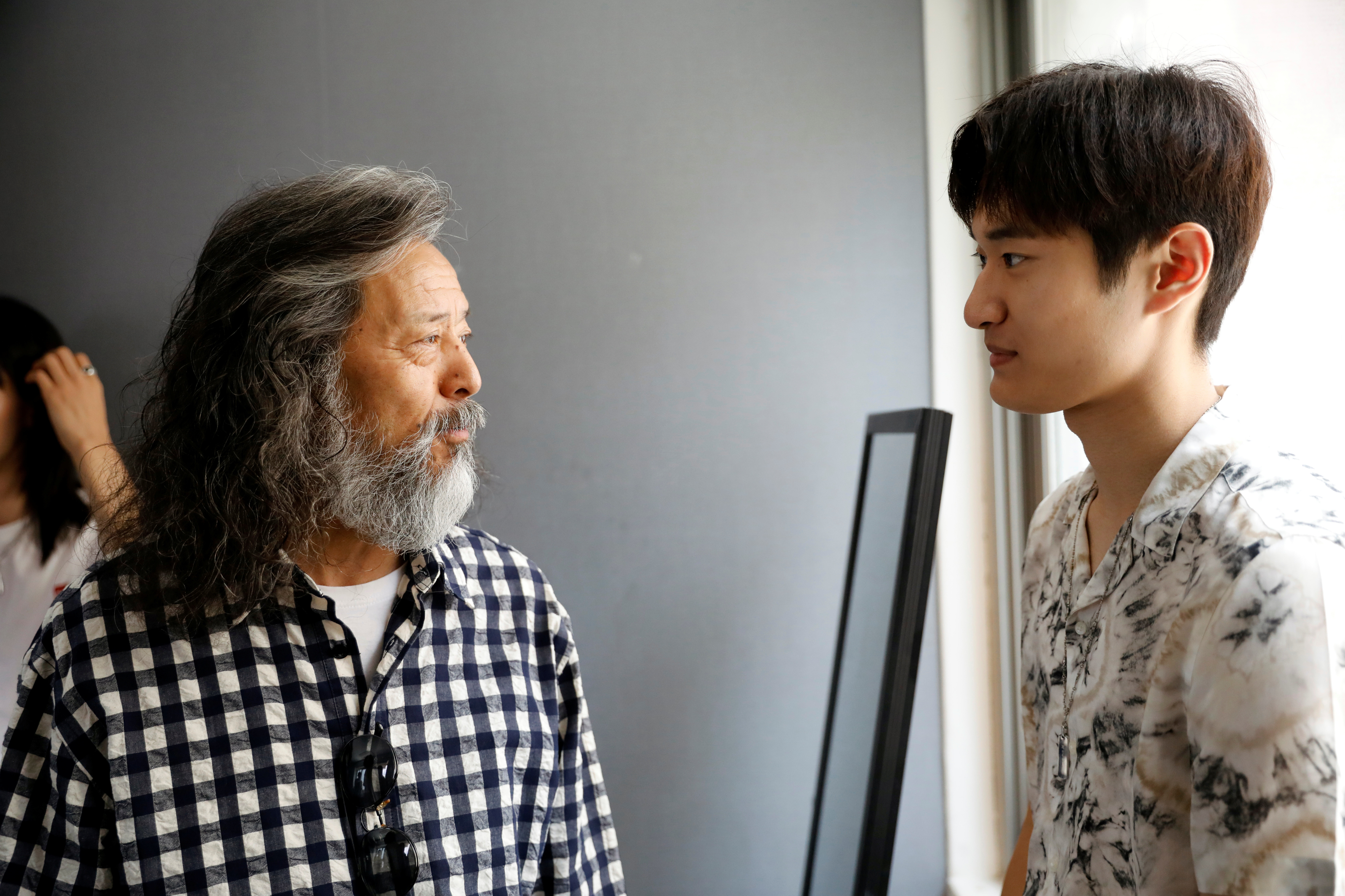 A South Korean senior model Kim Chil-doo, 65-years-old, talks with a younger model in Seoul, South Korea