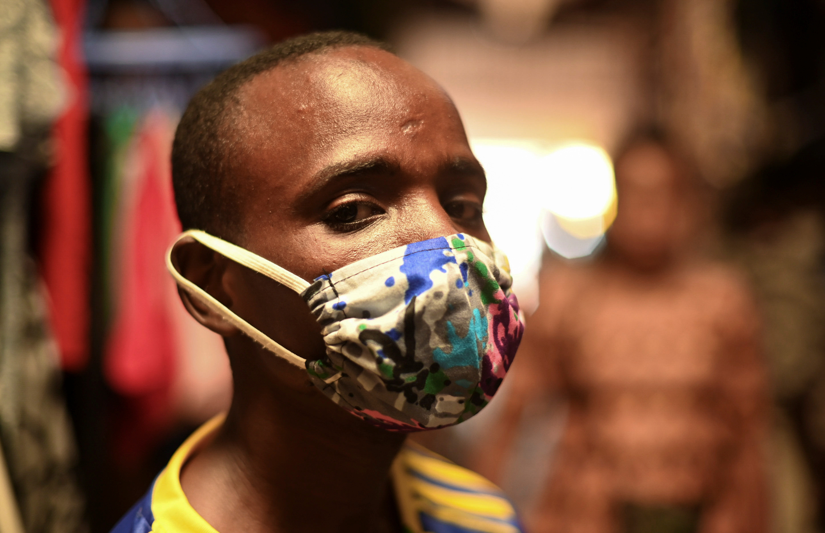 """Eugene Amuri, a vendor at the Kimironko market wears a handmade """"kitenge"""" cloth mask as he attempts to protect against the coronavirus disease (COVID-19), in Kigali, Rwanda March 17, 2020. REUTERS/Maggie Andresen - RC2TLF9JHIN5"""