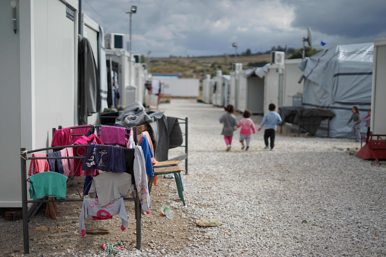 Children walking refugee camp, holding hands.