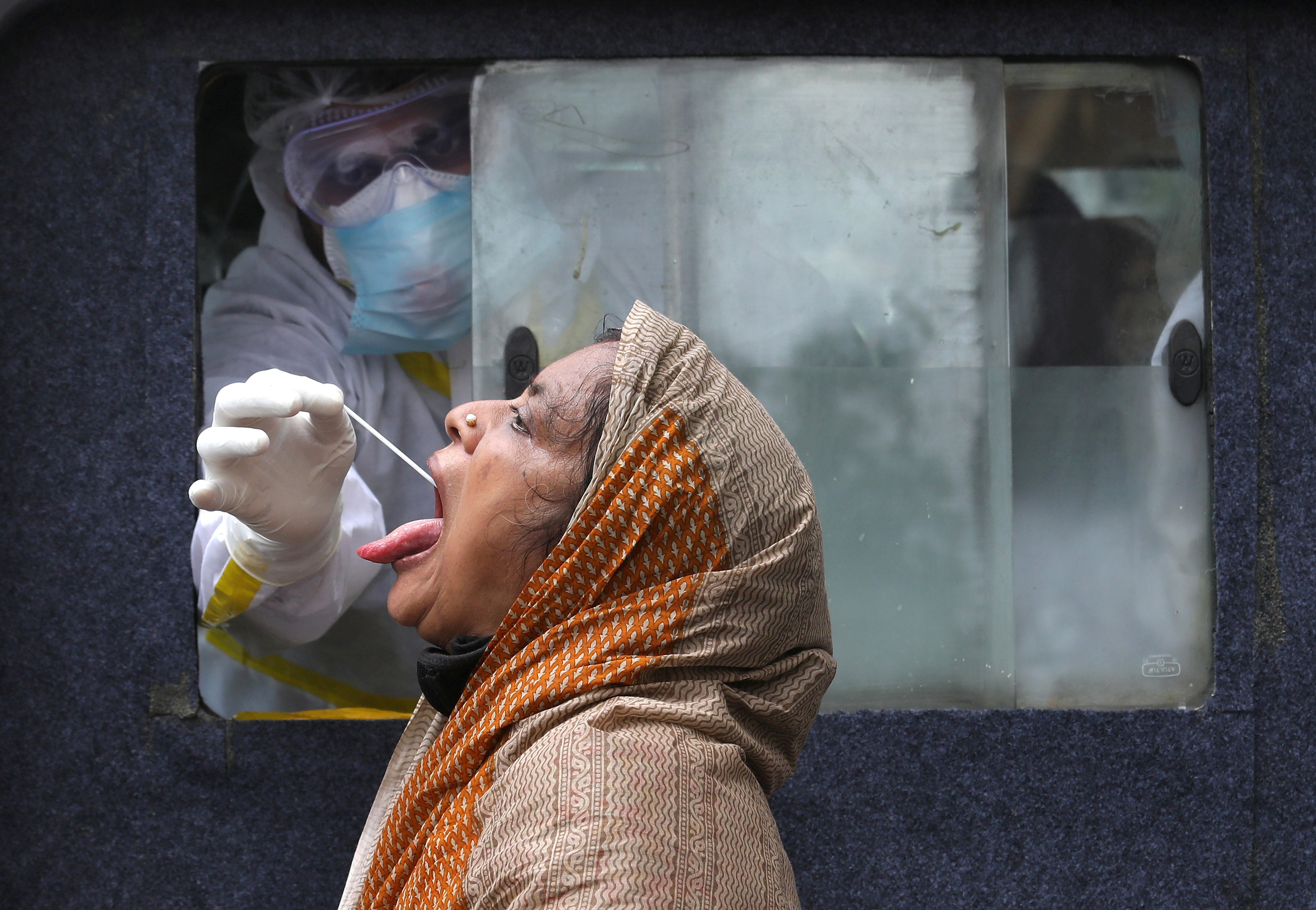 A woman reacts as a healthcare worker sitting inside an ambulance takes a swab from her to test for the coronavirus disease (COVID-19) in Kolkata, India, July 1, 2020. REUTERS/Rupak De Chowdhuri     TPX IMAGES OF THE DAY - RC28KH9TQ5U2
