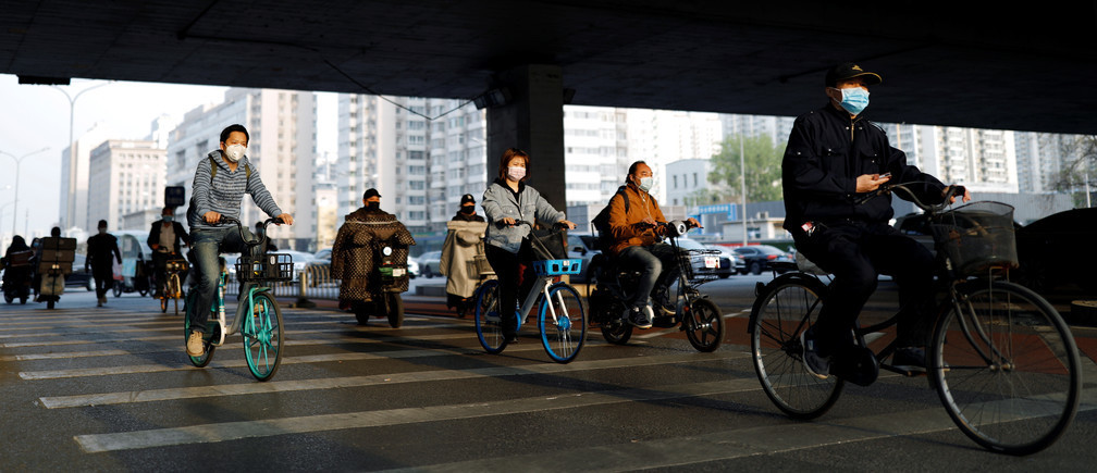 People wearing protective face masks ride bicycles and scooters on a street, following an outbreak of the coronavirus disease (COVID-19), in Beijing, China April 7, 2020. REUTERS/Carlos Garcia Rawlins - RC2MZF9BMYYS