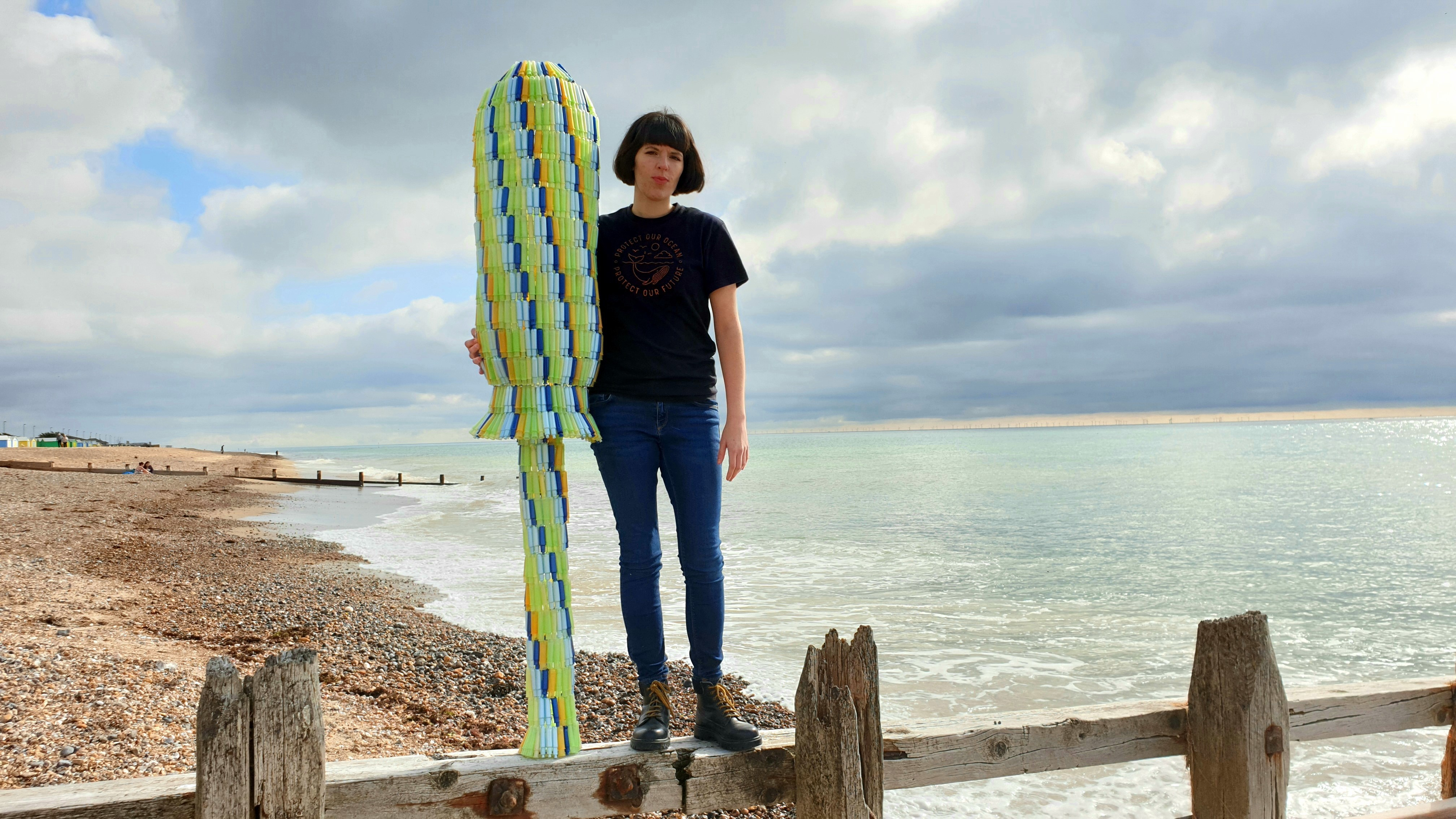 Ella Daish with a giant tampon applicator made from discarded plastic applicators found on British beaches