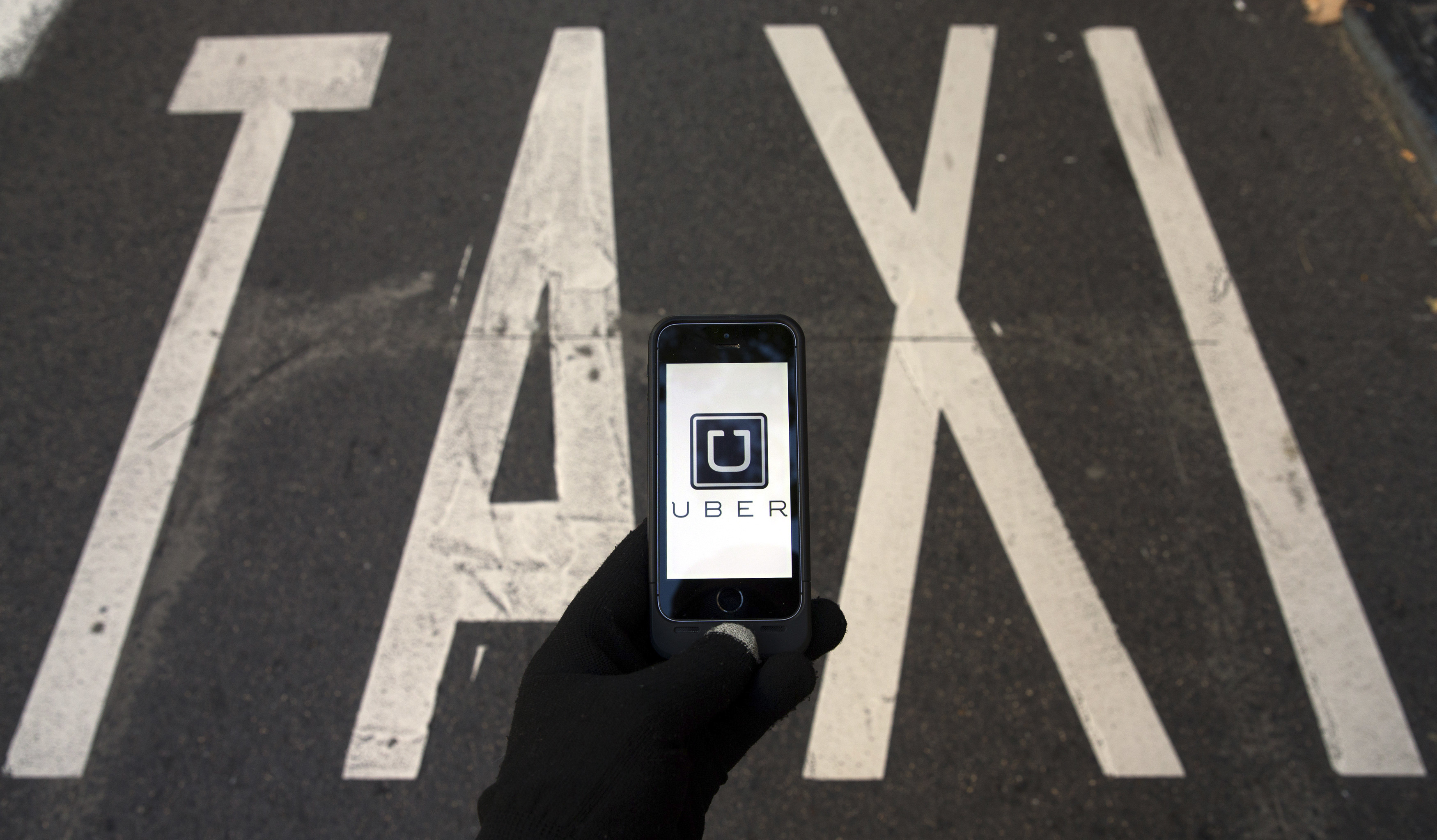The logo of car-sharing service app Uber on a smartphone over a reserved lane for taxis