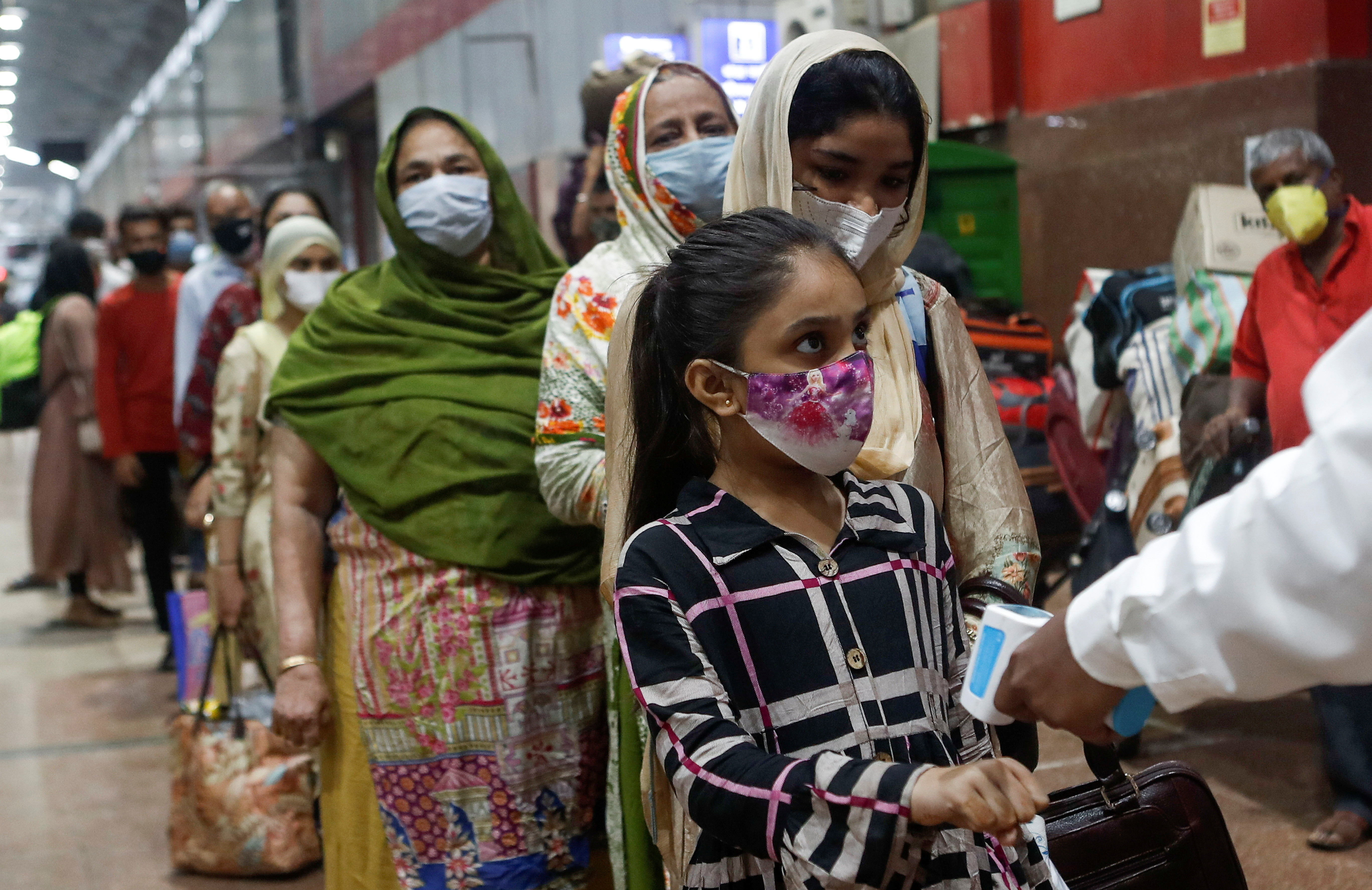 Passengers wait in line to get their temperature checked at a railway station, amid the spread of the coronavirus disease (COVID-19), in Mumbai, India November 26, 2020. REUTERS/Francis Mascarenhas - RC2XAK92D1AC