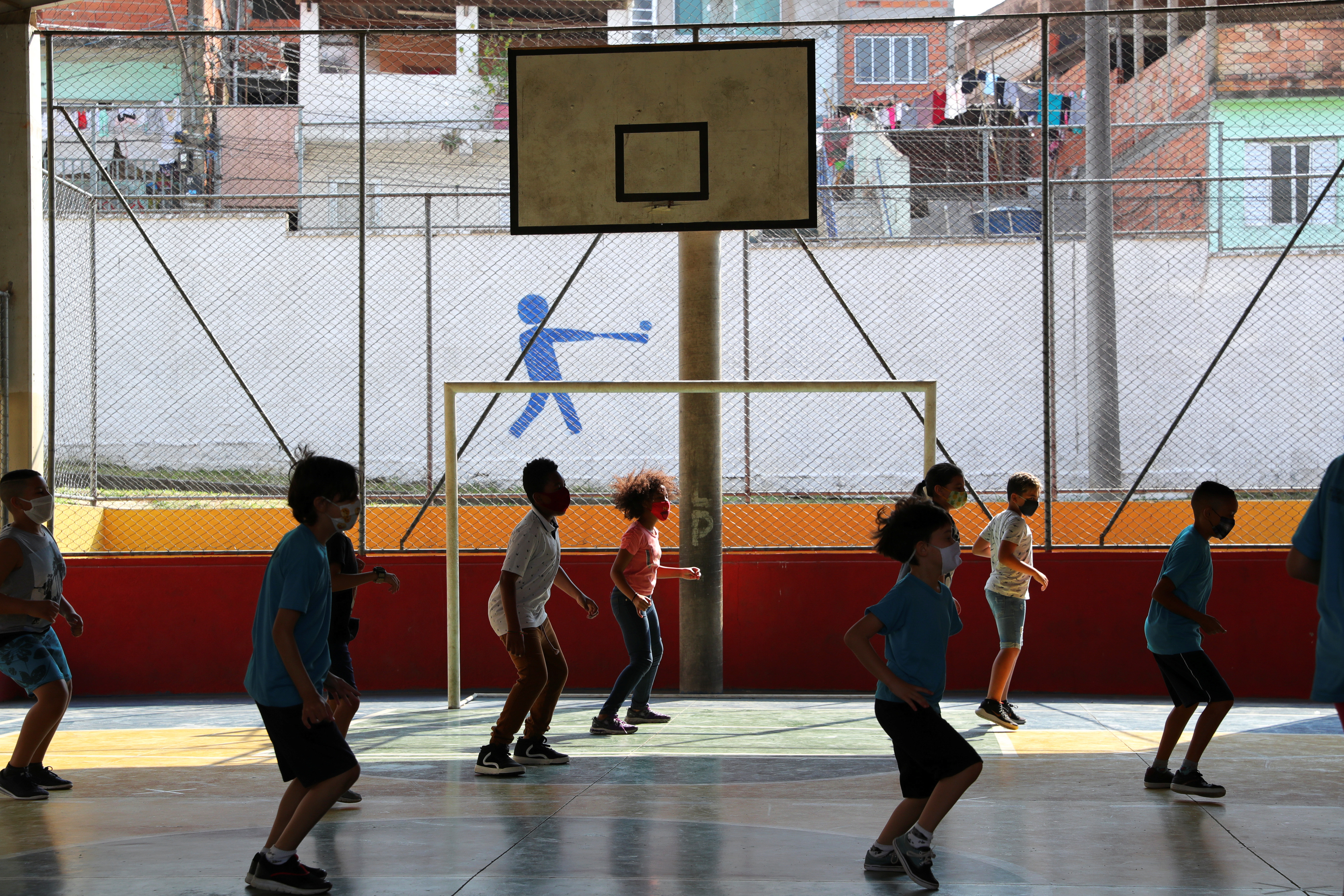 children perform exercise in a sports hall whilst wearing face masks