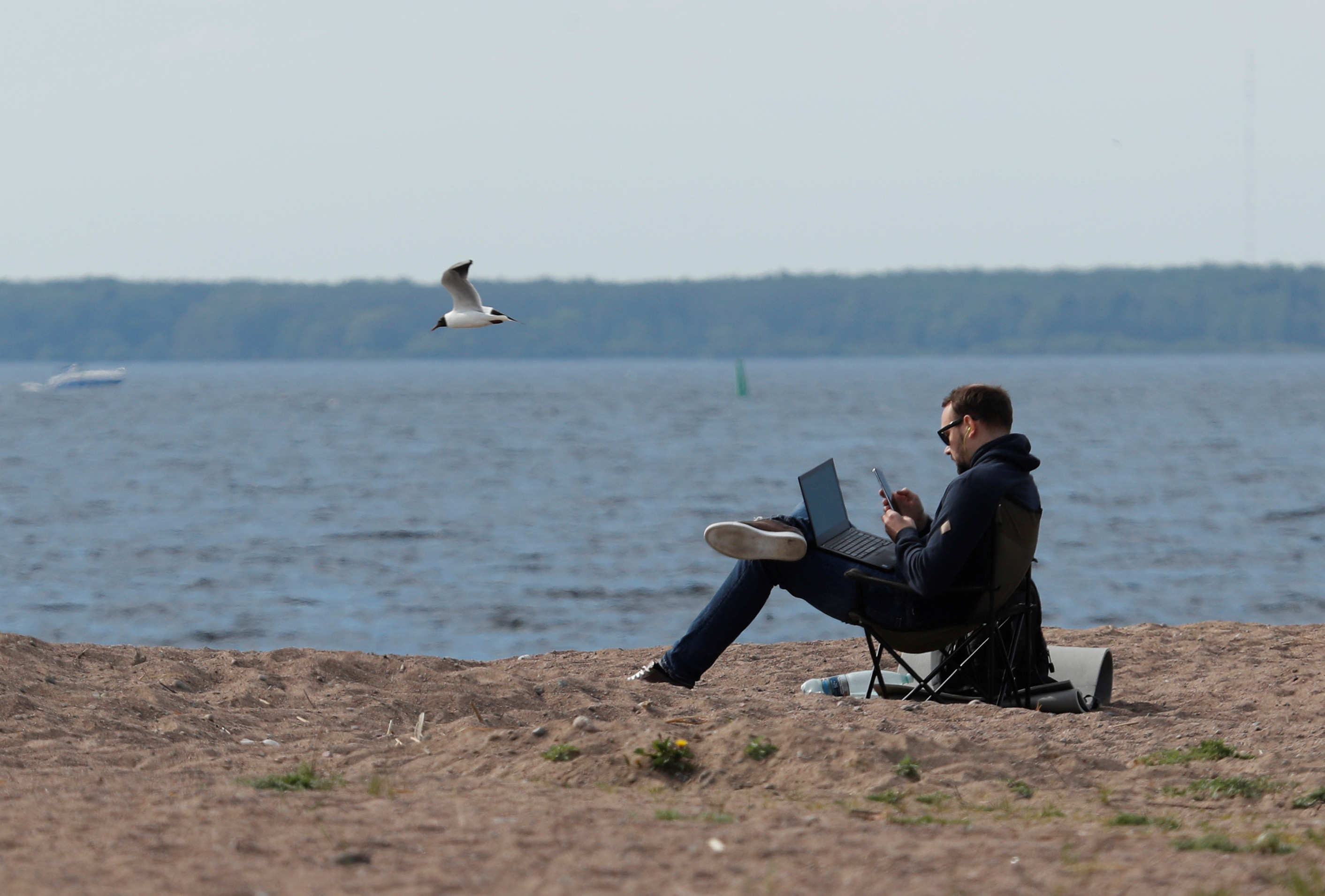 A man uses his smartphone and laptop as he sits on the shore of the Gulf of Finland amid the outbreak of the coronavirus disease (COVID-19) in Saint Petersburg, Russia May 27, 2020. REUTERS/Anton Vaganov - RC27XG94BMPU