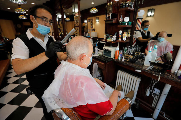 Igor Khaimov gives a customer a haircut at the Little Tony & Igor Be Good Barber Shop in Manhattan, on the first day of the phase two re-opening of businesses following the outbreak of the coronavirus disease (COVID-19), in New York City, New York, U.S., June 22, 2020. REUTERS/Mike Segar