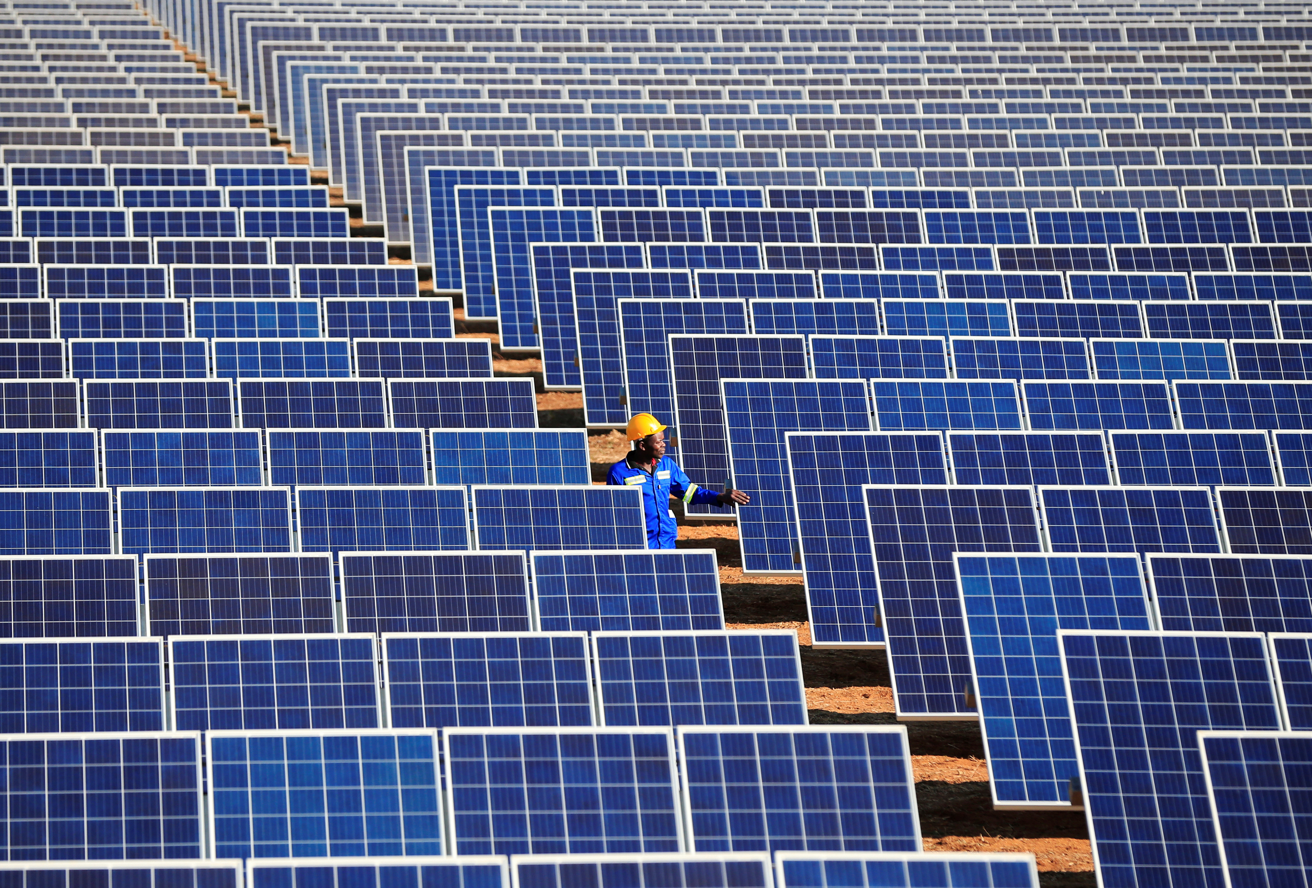 A worker walks between solar panels at Centragrid power plant in Nyabira, Zimbabwe, June 23, 2020