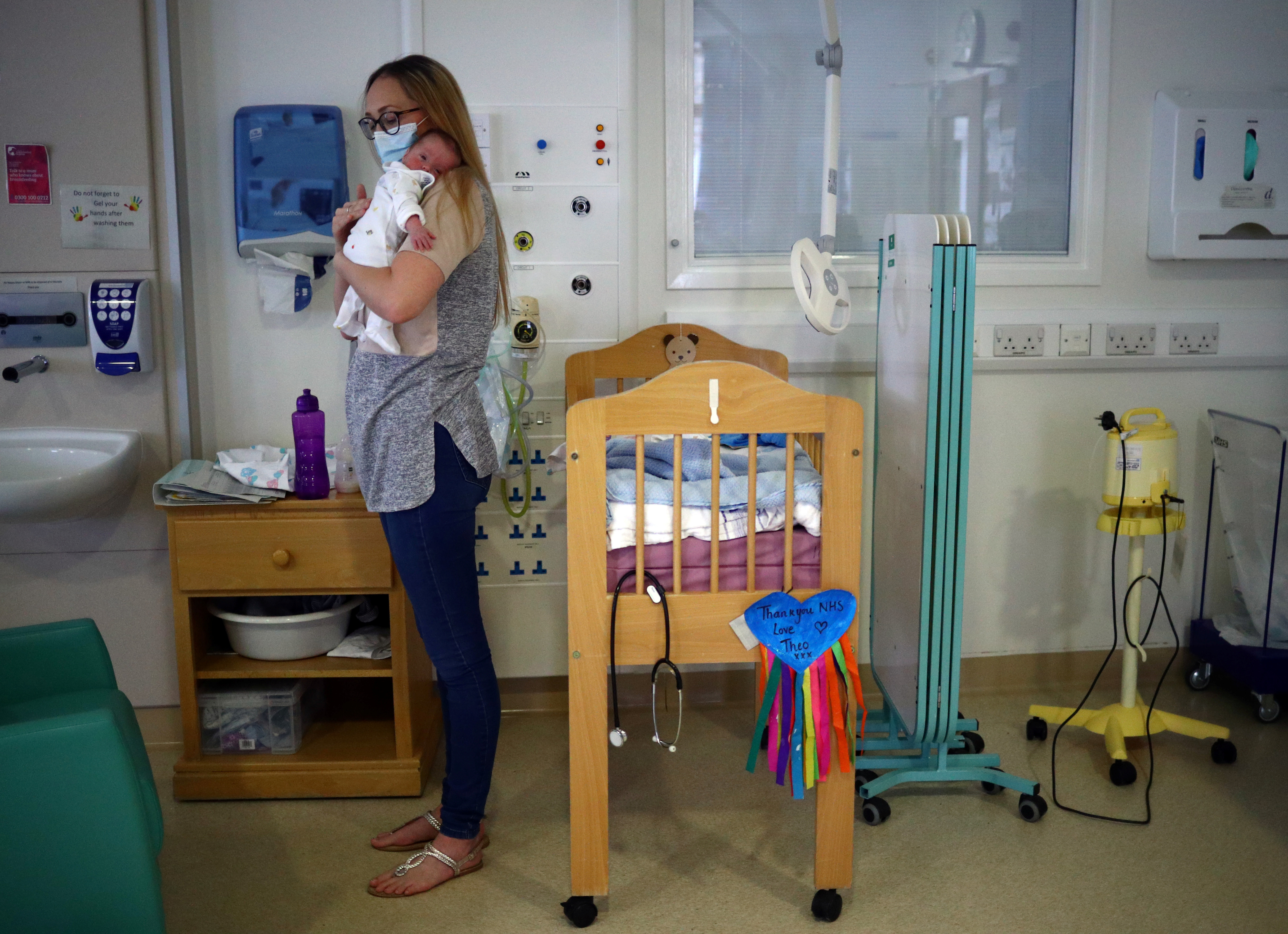 Kirsty Anderson holds her baby Theo, who was born prematurely and is now nine weeks old, as they wait for medical staff to discharge him from hospital in the Lancashire Women and Newborn Centre of Burnley General Hospital in East Lancashire, following the spread of the coronavirus disease (COVID-19) in Burnley, Britain, June 22, 2020. Picture taken June 22, 2020. REUTERS/Hannah McKay - RC2KFH9AI8TW