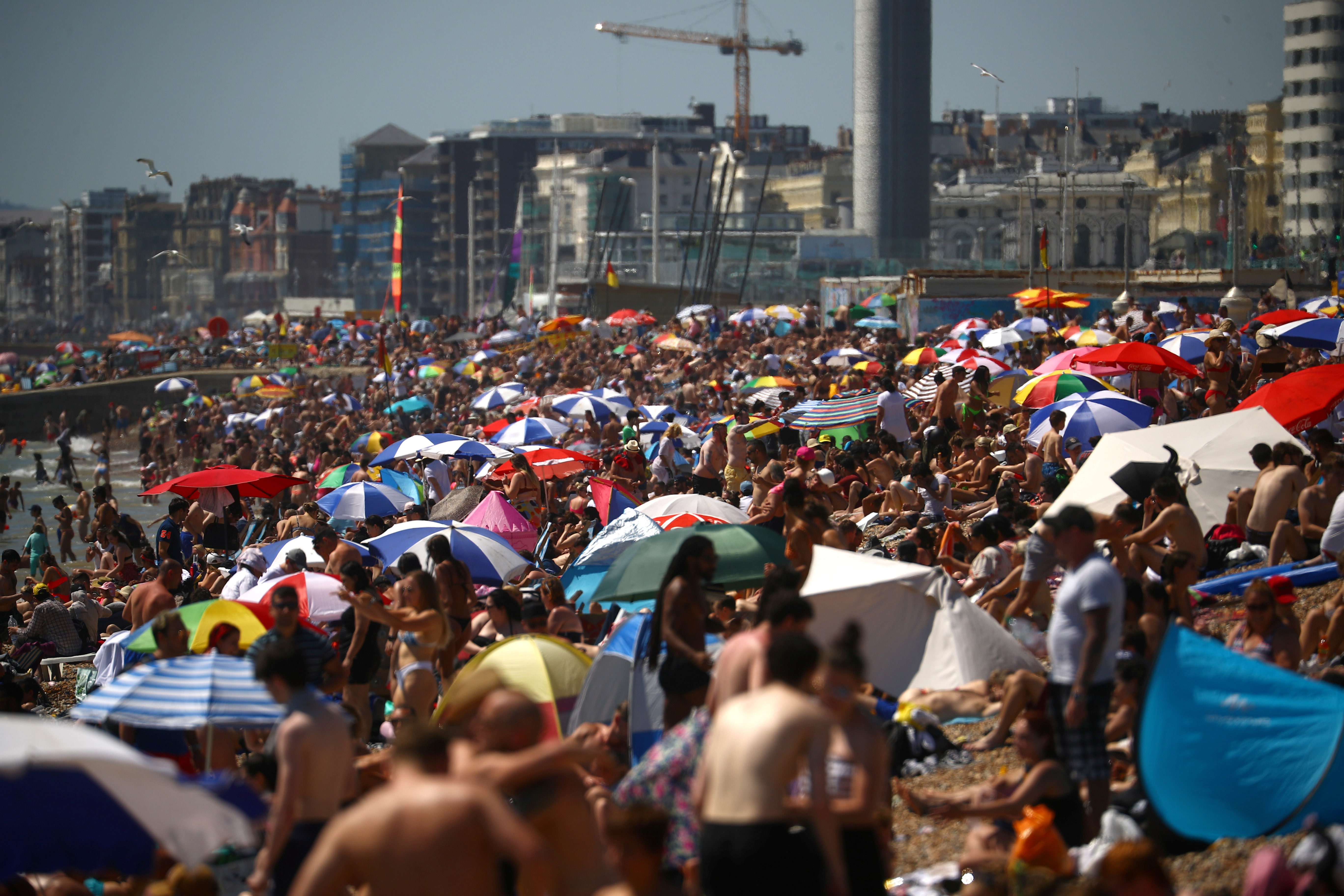 People enjoy the hot weather at the beach in Brighton, Britain, June 25, 2020. REUTERS/Hannah McKay - RC2DGH97DP5P