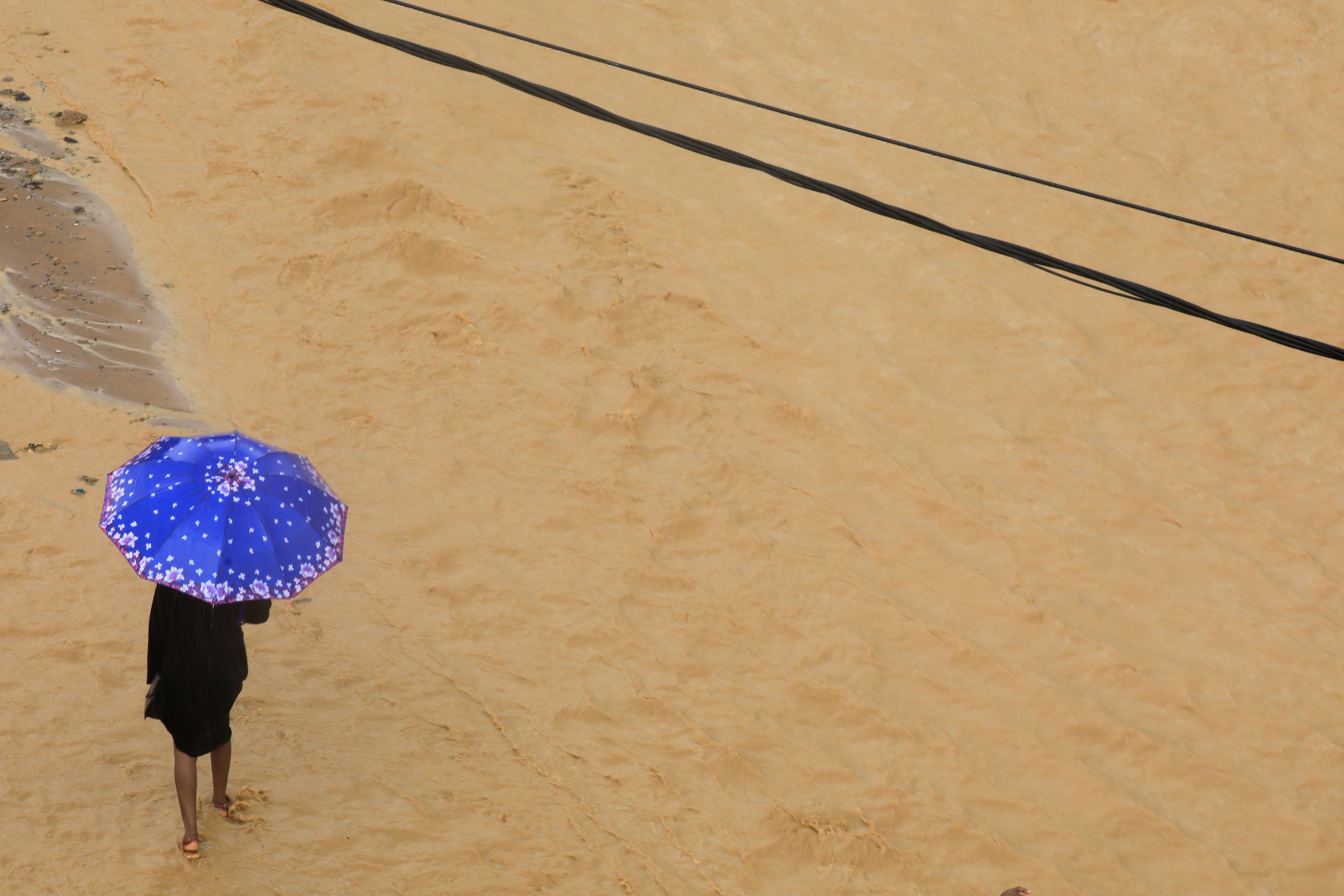 A girl with a blue umbrella is seen in a flooded street in Palmeraie, a neighbourhood of Abidjan, Ivory Coast, June 25, 2020. REUTERS/Thierry Gouegnon - RC2KGH9ASGWP