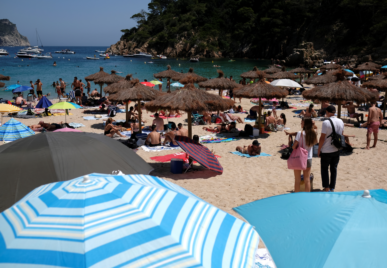 A couple (R) look at people enjoying sunny weather on Cala Aiguablava beach, amid the coronavirus disease (COVID-19) outbreak in Begur, near Girona, Costa Brava, Spain June 27, 2020. REUTERS/Nacho Doce - RC20IH95QE0N