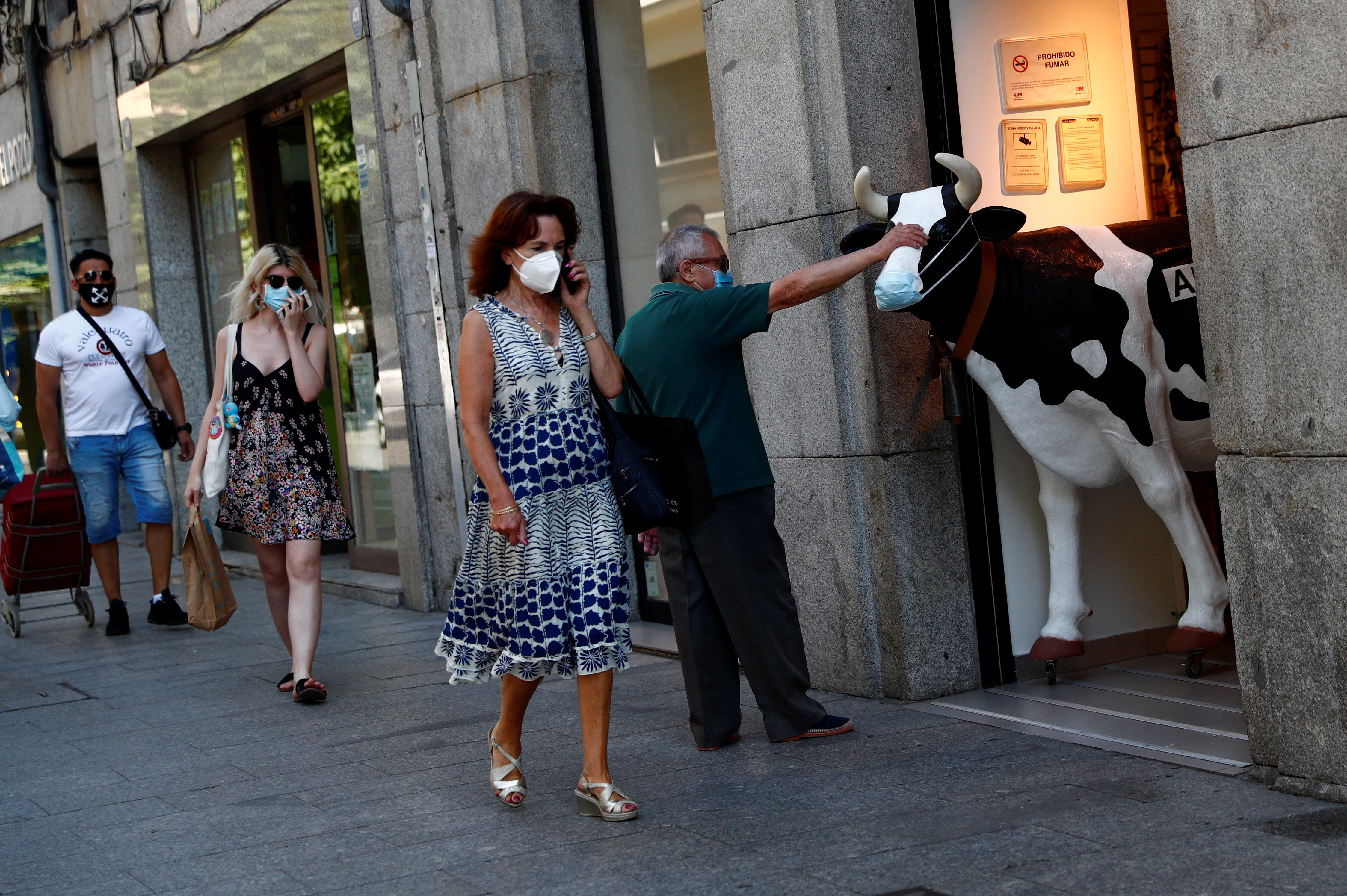 A man touches the face of a figure of a cow wearing a protective mask outside a store, amid the coronavirus disease (COVID-19) outbreak, in Madrid, Spain, June 30, 2020. REUTERS/Susana Vera - RC2NJH9PVS1N