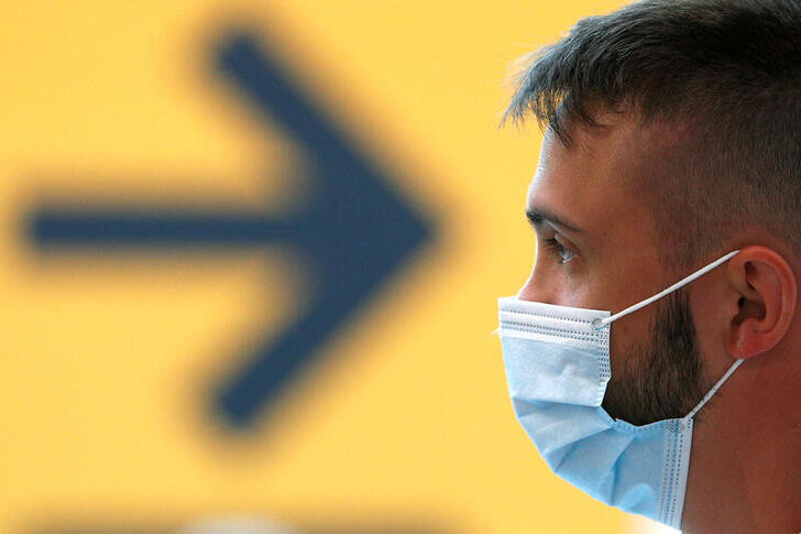 A passenger wearing a protective face mask waits for his flight at Fiumicino Airport, one of the two airports in the world to obtain the 'Biosafety Trust certification' for the correct application of security measures to prevent infections, following the coronavirus disease (COVID-19) outbreak, in Rome, Italy June 30, 2020. REUTERS/Guglielmo Mangiapane