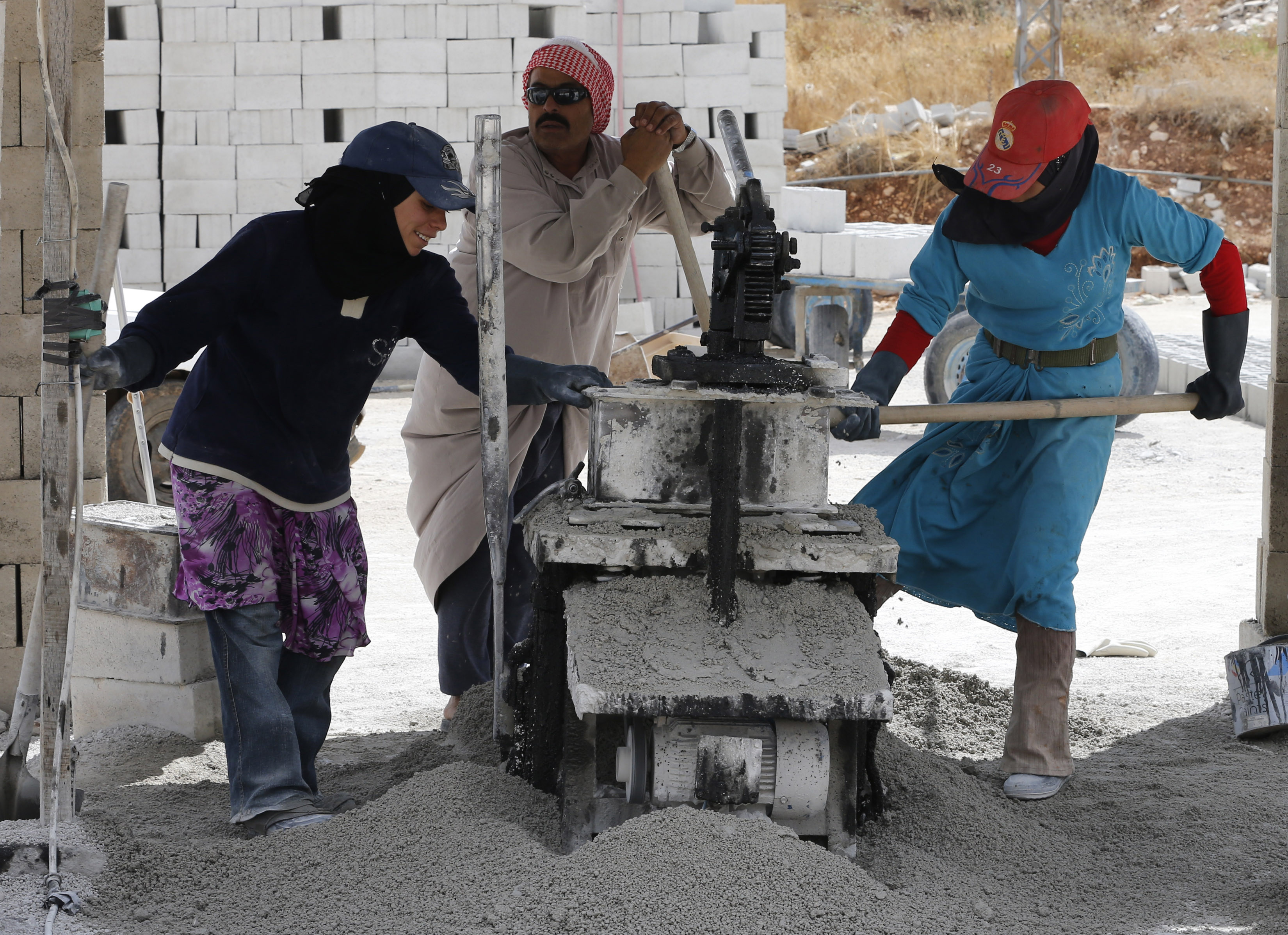 Syrian refugees work to help produce concrete blocks in Bekaa Valley, Lebanon.