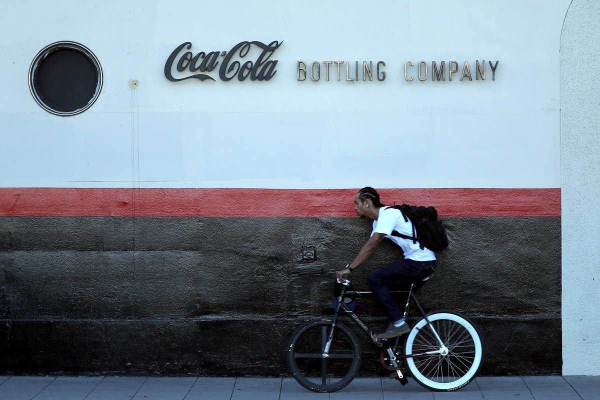 A man cycles past the Coca Cola bottling plant in Los Angeles, California, U.S. October 24, 2017. REUTERS/Lucy Nicholson - RC18A6259170