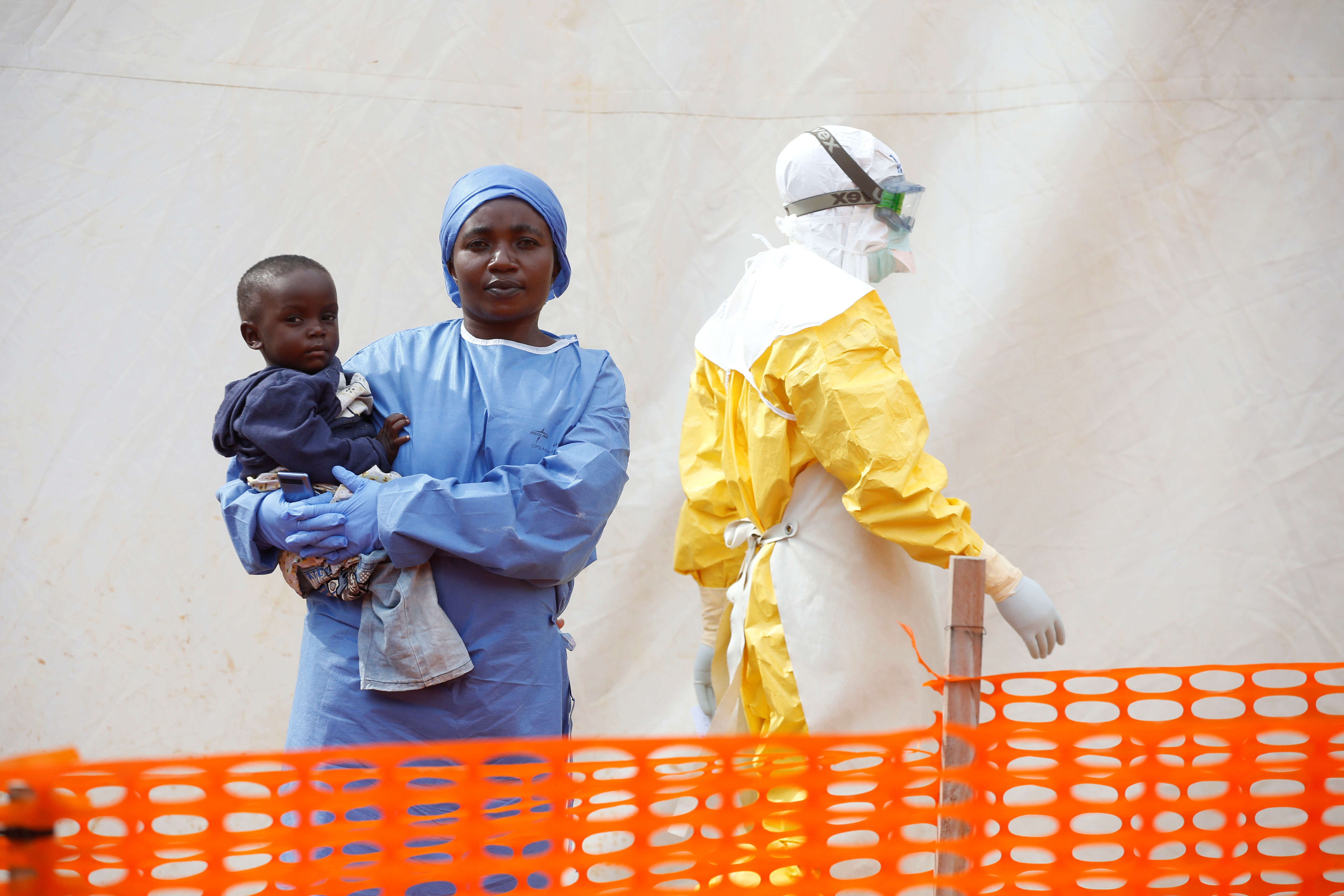 Mwamini Kahindo, an Ebola survivor working as a caregiver to babies who are confirmed Ebola cases, holds an infant outside the red zone at the Ebola treatment centre in Butembo, Democratic Republic of Congo, March 25, 2019. Picture taken March 25, 2019. REUTERS/Baz Ratner - RC1F947ED5F0