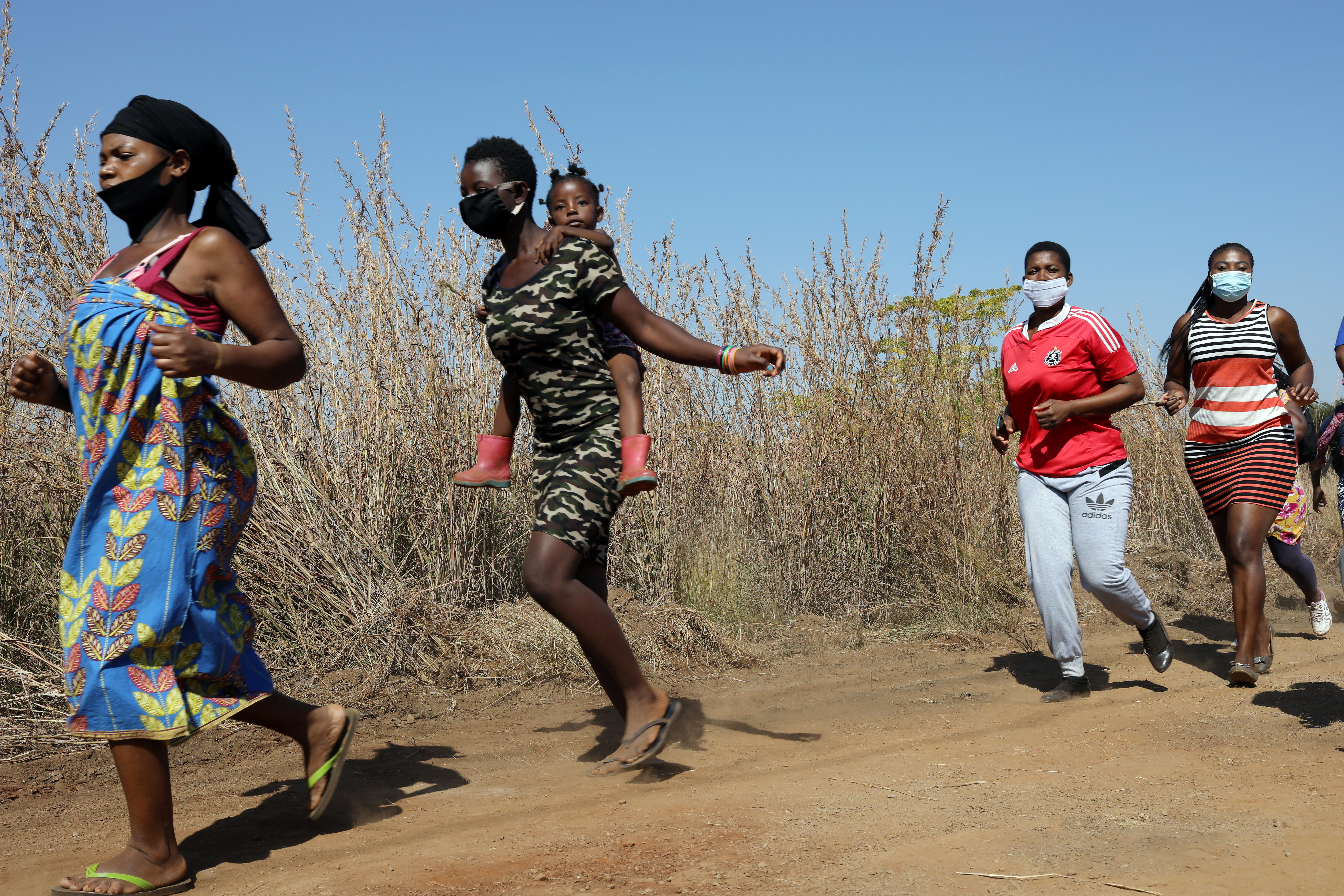 Women and children run to receive food aid amid the spread of  the coronavirus disease (COVID-19) outbreak, at the Itireleng informal settlement, near Laudium suburb in Pretoria, South Africa, May 20, 2020. REUTERS/Siphiwe Sibeko - RC2BSG9AN9D6