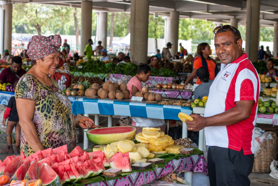 Woman serving a man fruit in a PNG market place.