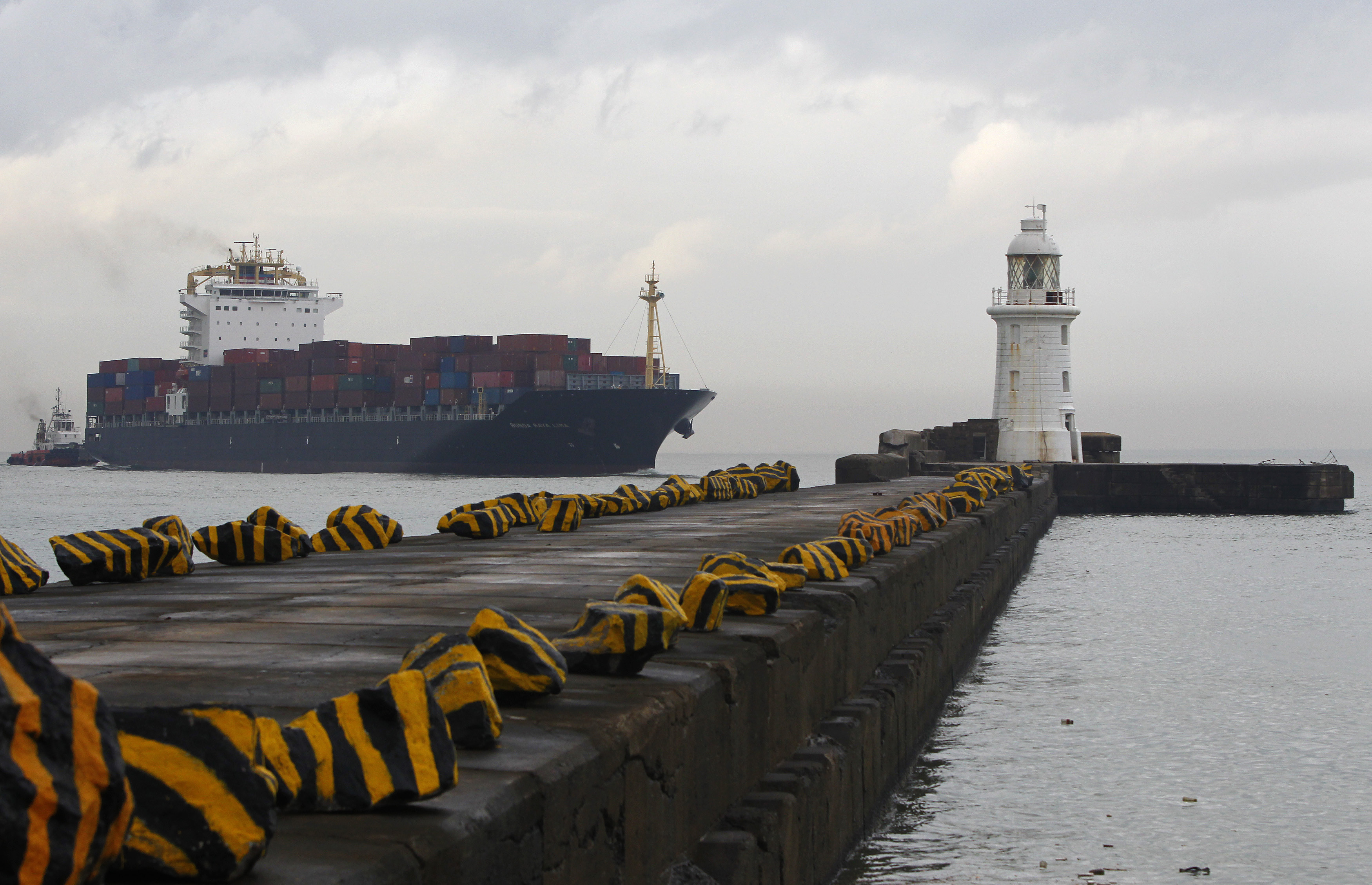 A container ship passes a lighthouse as it enters the main Sri Lankan port in Colombo December 8, 2010.   In the country's 2011 budget over $6 billion in post-war infrastructure projects have  been given priority with public investment of 413.7 billion  rupees ($3.7 billion) budgeted in 2011. Offshore investors  have long complained about Sri Lanka's poor infrastructure, so  the moves to boost ports and build roads have been welcomed.  REUTERS/Andrew Caballero-Reynolds  (SRI LANKA - Tags: BUSINESS) - GM1E6C81ORI01