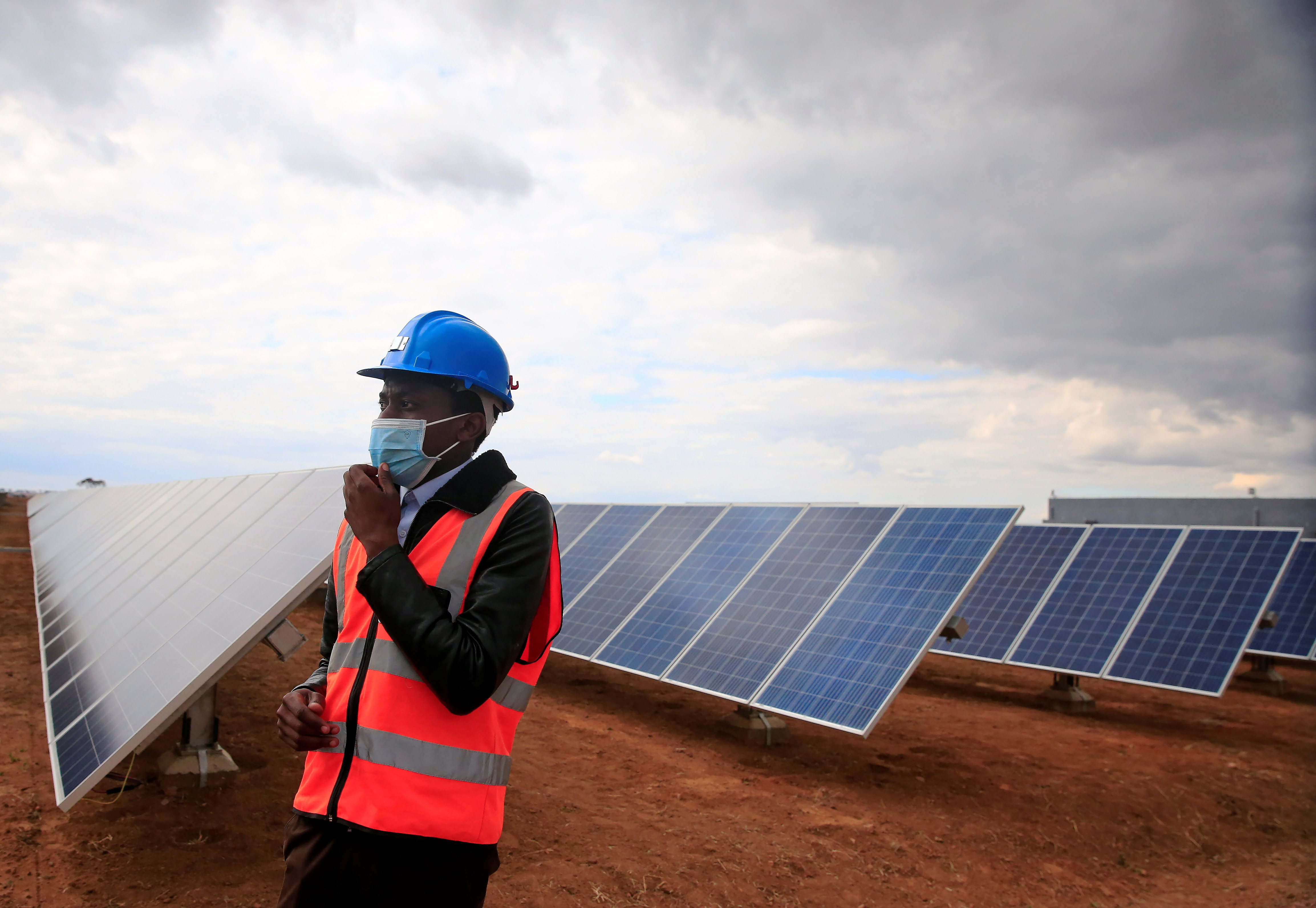 A worker walks past solar panels at Centragrid power plant in Nyabira, Zimbabwe, June 22, 2020