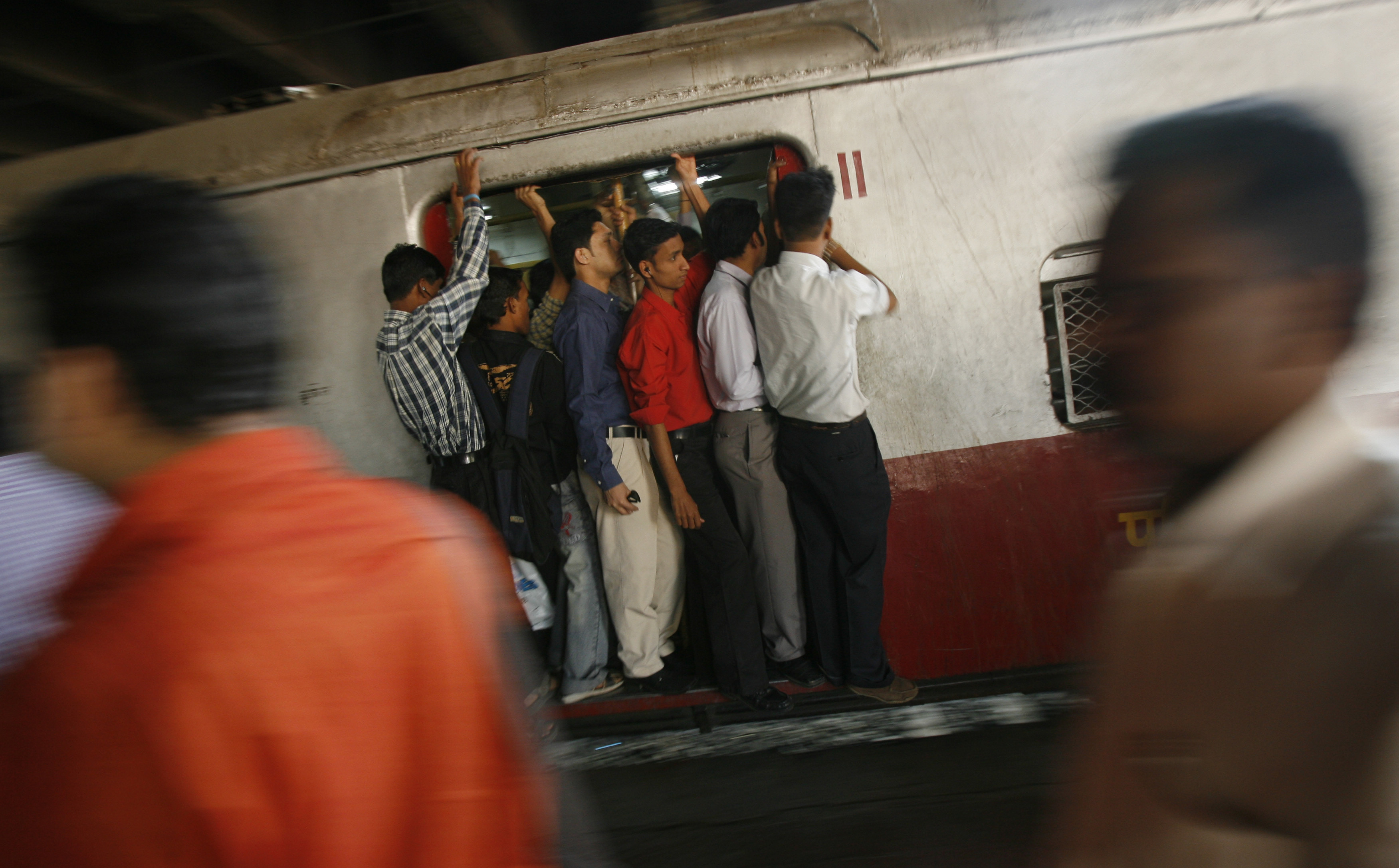 Passengers travel in a crowded suburban train at a railway station in Mumbai February 26, 2008. India's Railways Minister Lalu Prasad Yadav announced a cut of 50 rupees ($1.25) in passenger fares for express trains as he presented the annual budget for one of the world's largest networks on Tuesday.   REUTERS/Arko Datta (INDIA) - GM1E42Q1DYJ01