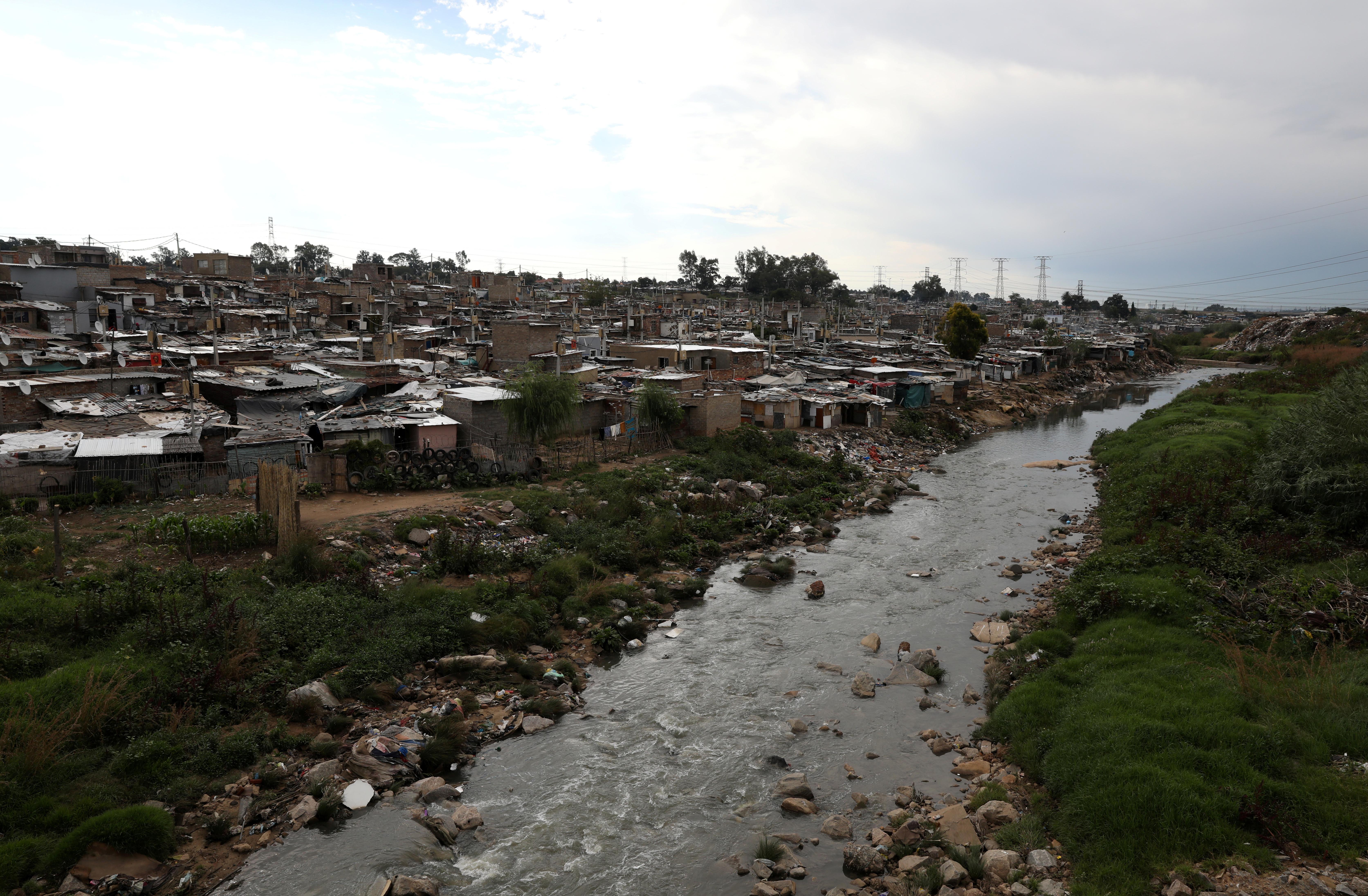 Shacks are seen along Jukskei river in Alexandra township, Johannesburg, South Africa